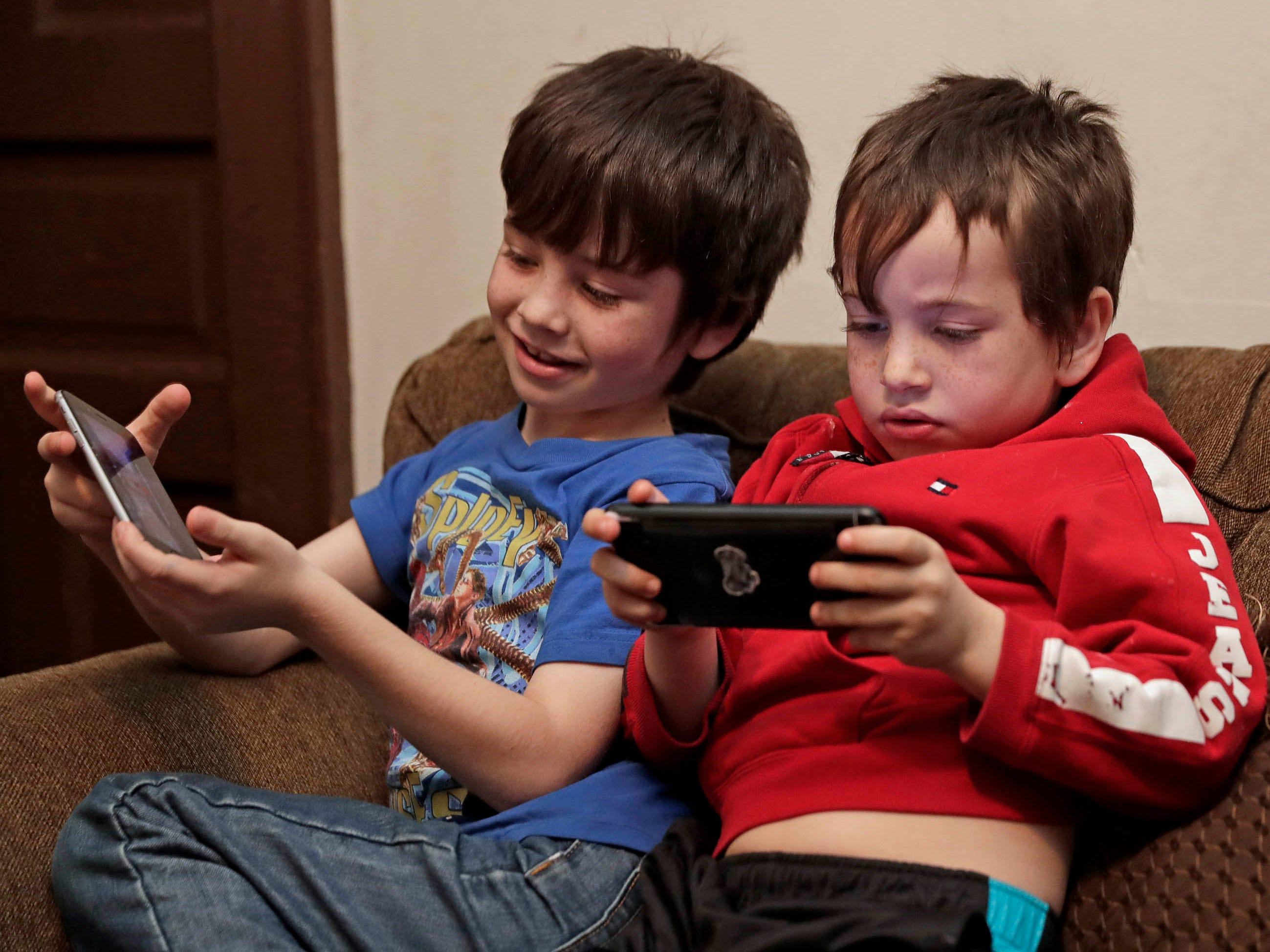 Mohannad Hamdoun, 7, and his brother, Yousif, 5, play video games.