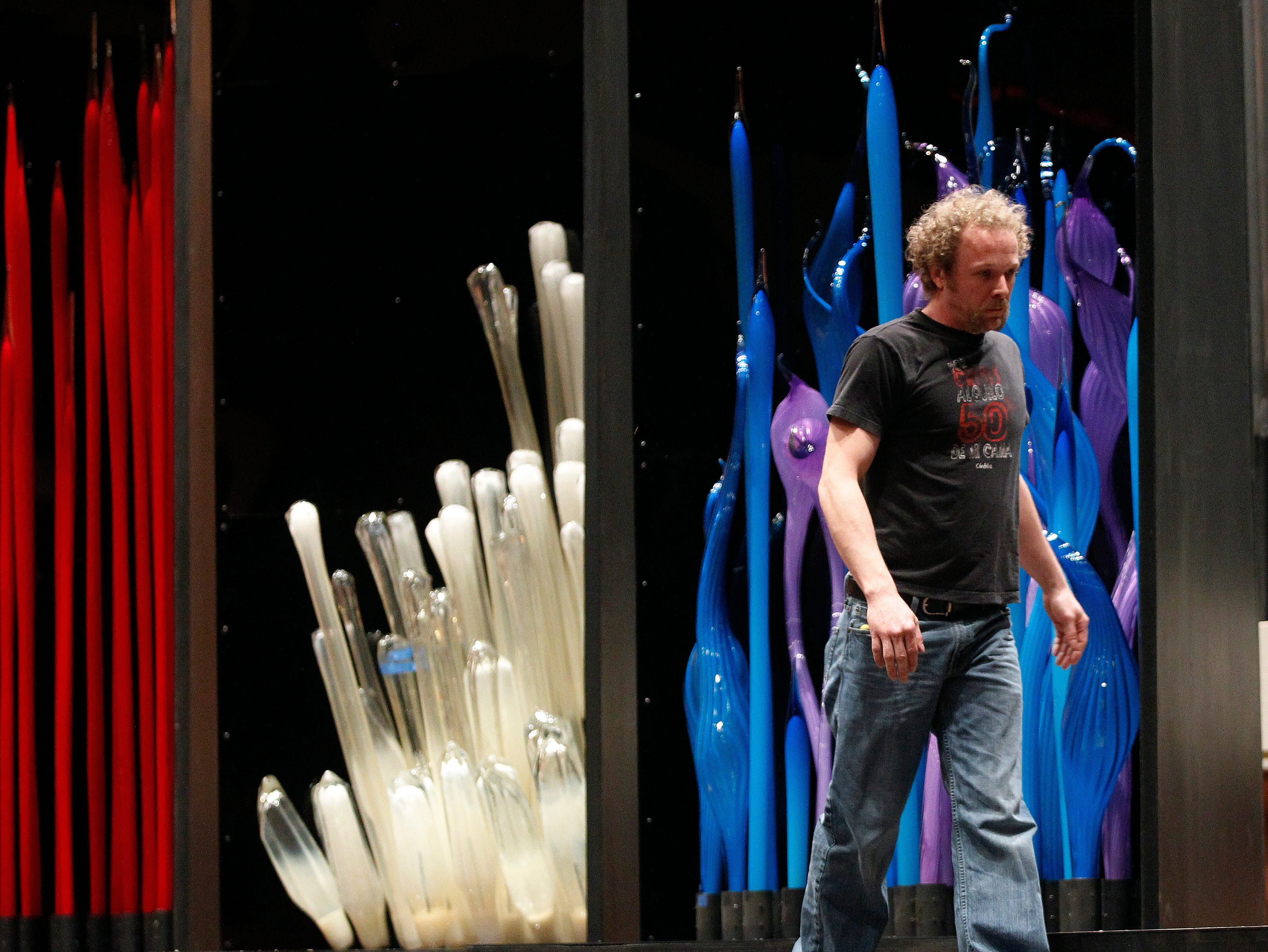 """Dustin Ashlock walks past three complete displays while setting up seven large Dale Chihuly glass sculptures Tuesday, March 12, 2013 at the Marcus Center for the Performing Arts in Milwaukee, Wis.  Ashlock works for Dale Chihuly. The sculptures will be incorporated in to the Milwaukee Symphony Orchestra's  weekend performances of  Bartok's """"Bluebeard's Castle"""" and Mozart's Concerto No. 2 in E-flat major for Horn and Orchestra. The sculptures, which Chihuly said consist of 176 pieces of glass, some up to 15 feet long, was be shipped from Washington state and accompanied by a setup crew. Weighing in at about 9,000 pounds, the sets have been seen in performances in Seattle, Nashville and Tel Aviv.  MARK HOFFMAN/MHOFFMAN@JOURNALSENTINEL.COM"""
