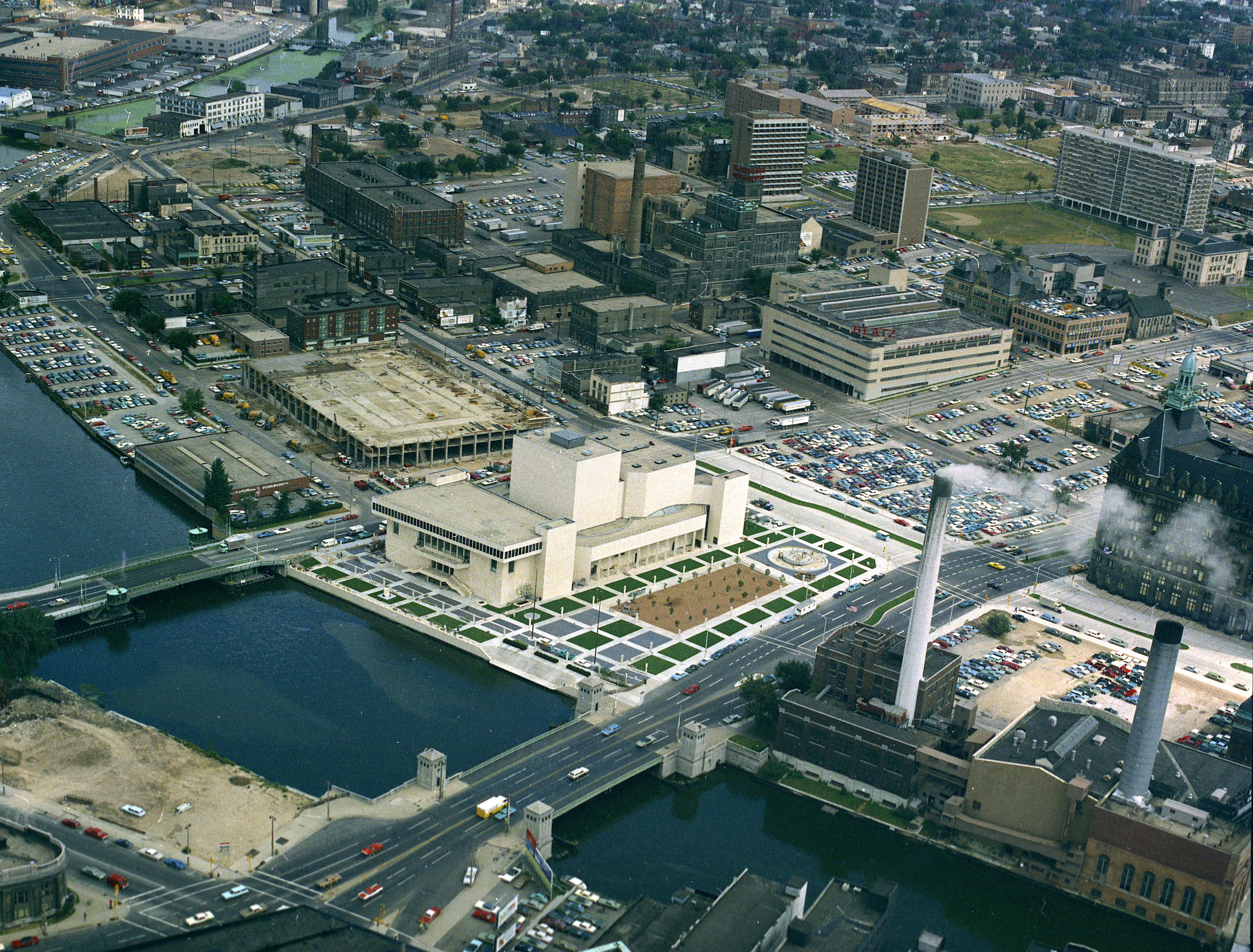 2x2 color film negative of the new Milwaukee Performing Arts Center (now known as the Marcus Center for the Performing Arts) or PAC at 929 N. Water St. Construction began on June 27, 1966, and it opened on July 26, 1969. This is an aerial photo of downtown west of the river looking northeast. In the background you can see the construction for the connected parking structure. Date is 9/8/1969  exterior, building, music, performance, stage, theater, Uihlein Hall, Todd Wehr hall, Peck Pavilion.