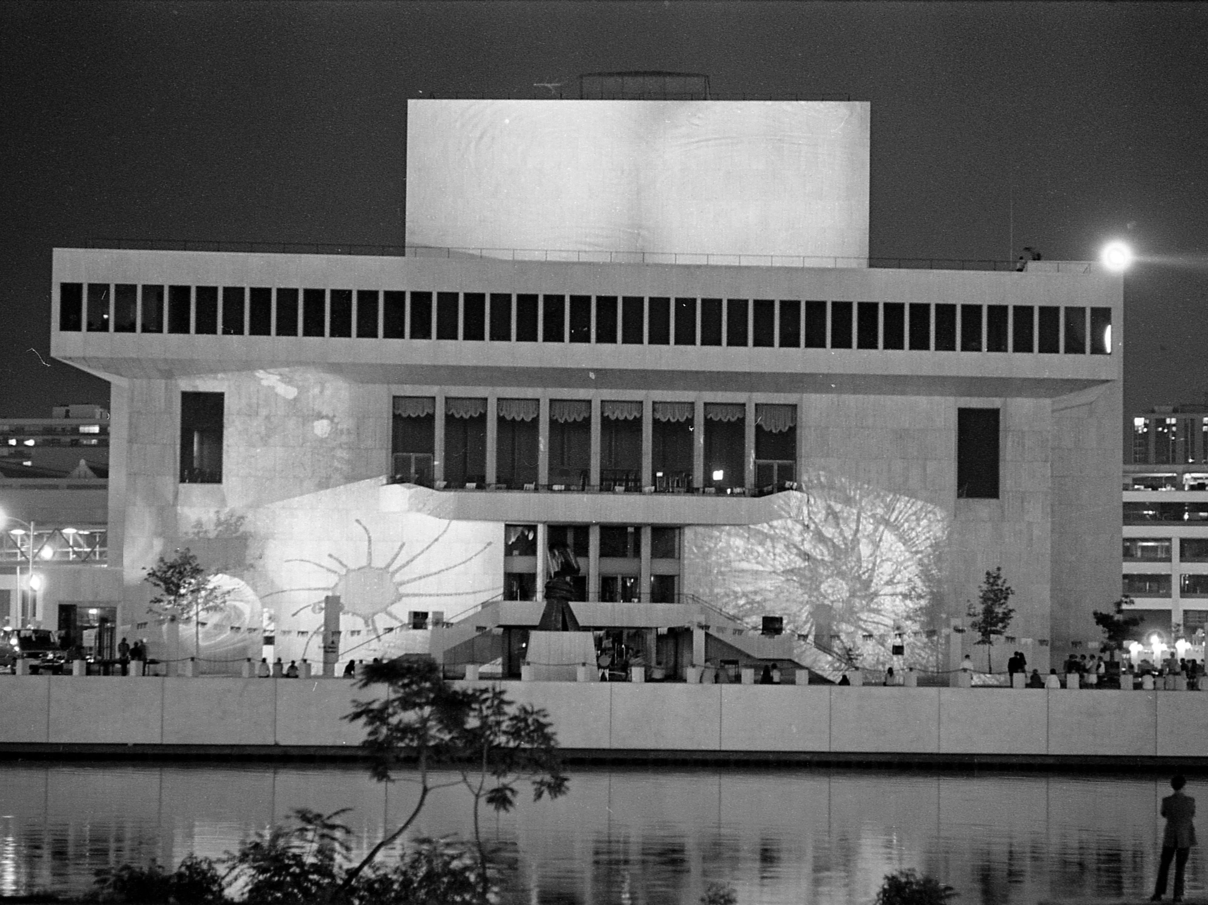 35mm film negative of a night shot of the new Milwaukee Performing Arts Center (now known as the Marcus Center for the Performing Arts) or PAC at 929 N. Water St. Construction began on June 27, 1966. This photo shows the west side of the exterior.  it was taken from across the river at Pere Marquette park and shows abstract images projected on the walls of the center.  Photo was filed 10/13/1969 Neg #69562 exterior, building, music, performance, stage, theater, Uihlein Hall, Todd Wehr hall, Peck Pavilion.