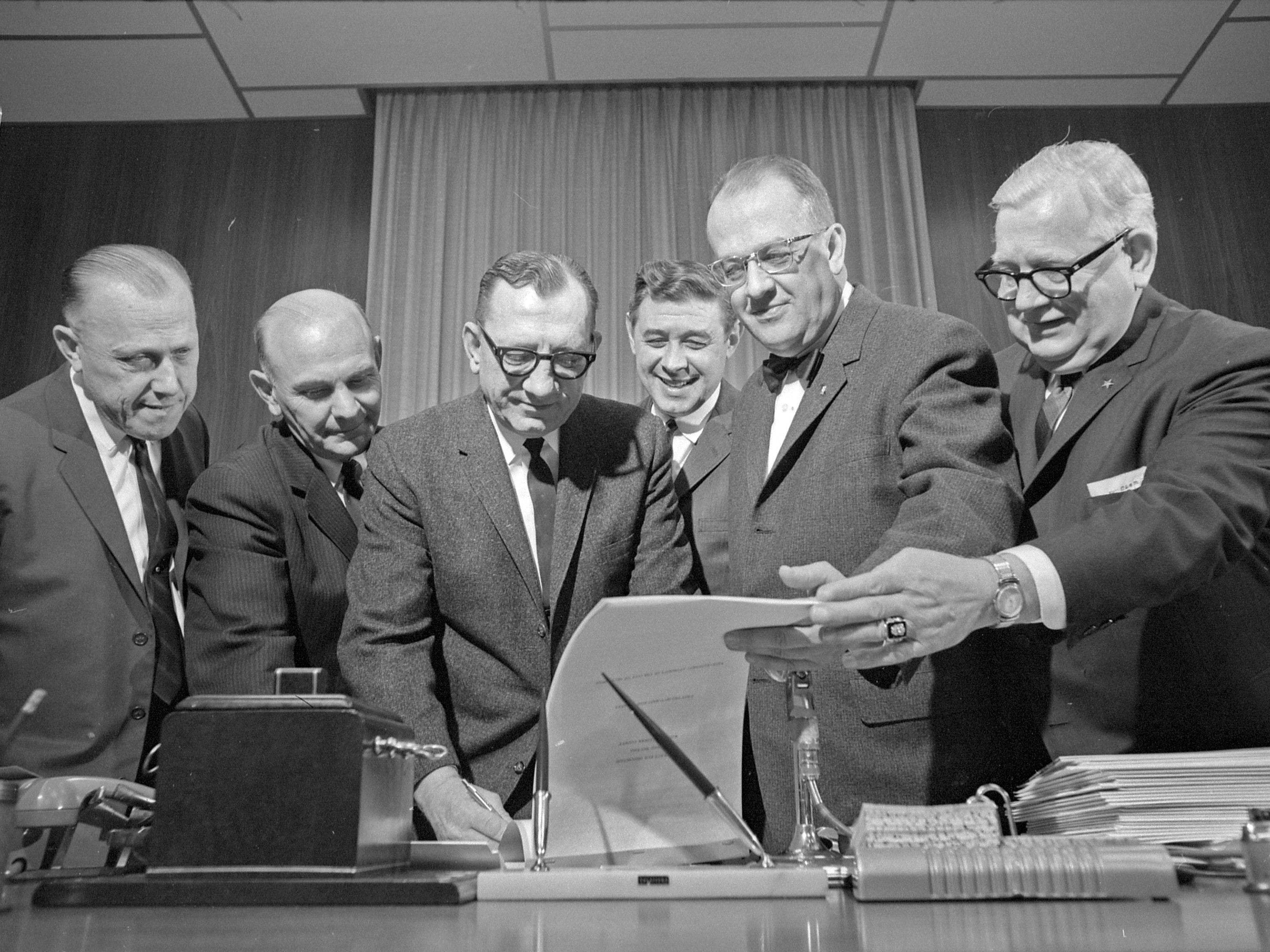 """35mm film negative of the signing of the contract for a proposed music hall, later to become the Performing Arts Center and now known as the Marcus Center for the Performing Arts. This photo was in the March 10th edition of the Journal with the caption """"A contract for sale of the site for the proposed music hall was signed Wednesday in city hall. The contract gives the county until December, 1966, to make actual purchase and take title to the land, now owned by the redevelopment authority. Sale price has been set at $514,000. Participating in the ceremony were (from left) Ald. Martin E. Schreiber, common council president; Eugene Grobschmidt, county board chairman, Ald. Robert L. Sulkowski, vice-chariman of the city redevelopment authority; Mayor Maier; Richard W.E. Perrin, director of city development, and County Clerk Clemens Michalski. The site is on the east side of the Milwaukee river and is bordered by E. Kilbourn av. and E. State and N. Water sts.""""  Date is 3/10/1965.  PAC  transparency folder #65653"""