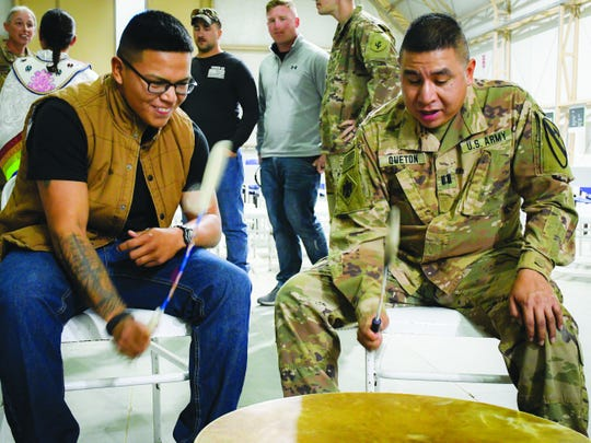 Army Pfc. Tayshaun Mingo, 21, and Capt. Warren Queton, 37, compete to stay on an increasingly fast beat on a traditional buffalo-hide drum at a powwow at Camp Buehring in Kuwait Nov. 27.