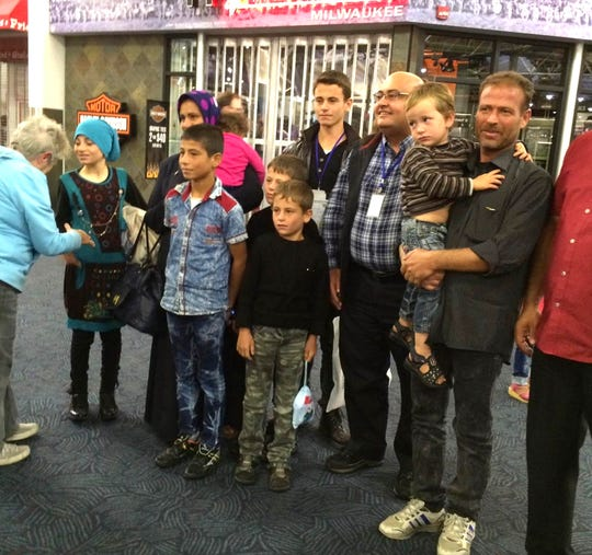Turki Hamdoun (holding one of his 11 children at right) arrives at the airport in Milwaukee in 2016. A group of classmates from the old Holy Angels Academy was there to meet the family and help get them settled in Milwaukee.