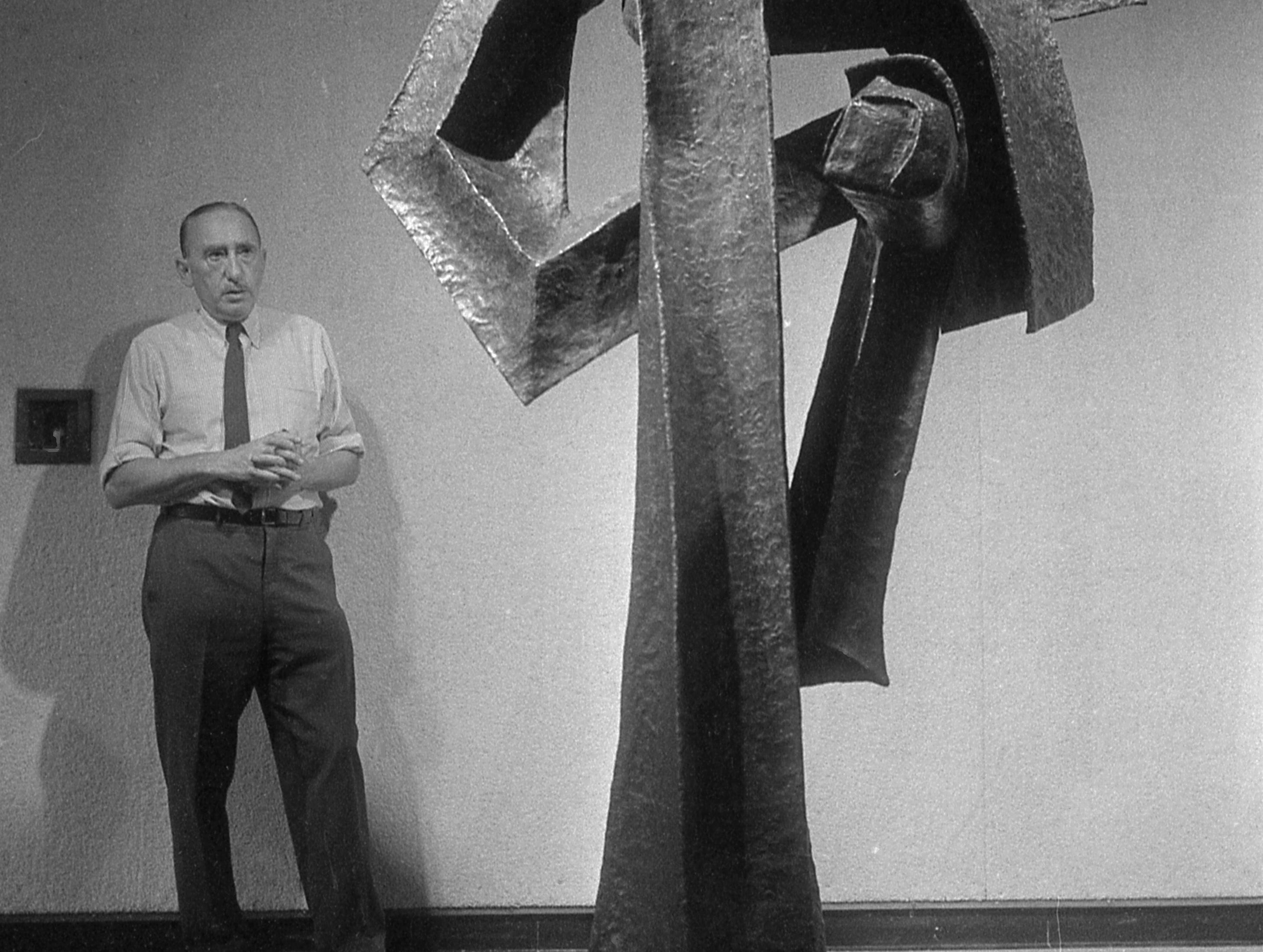 """35mm film negative of artist Seymour Lipton with one of his his scupltures (name unknown). Lipton was commissioned to create a work he called  """"Laureate"""" which was installed on the west side of the new Milwaukee Performing Arts Center (now known as the Marcus Center for the Performing Arts) or PAC at 929 N. Water St.  Photo was filed 10/23/1969  Neg#69593"""