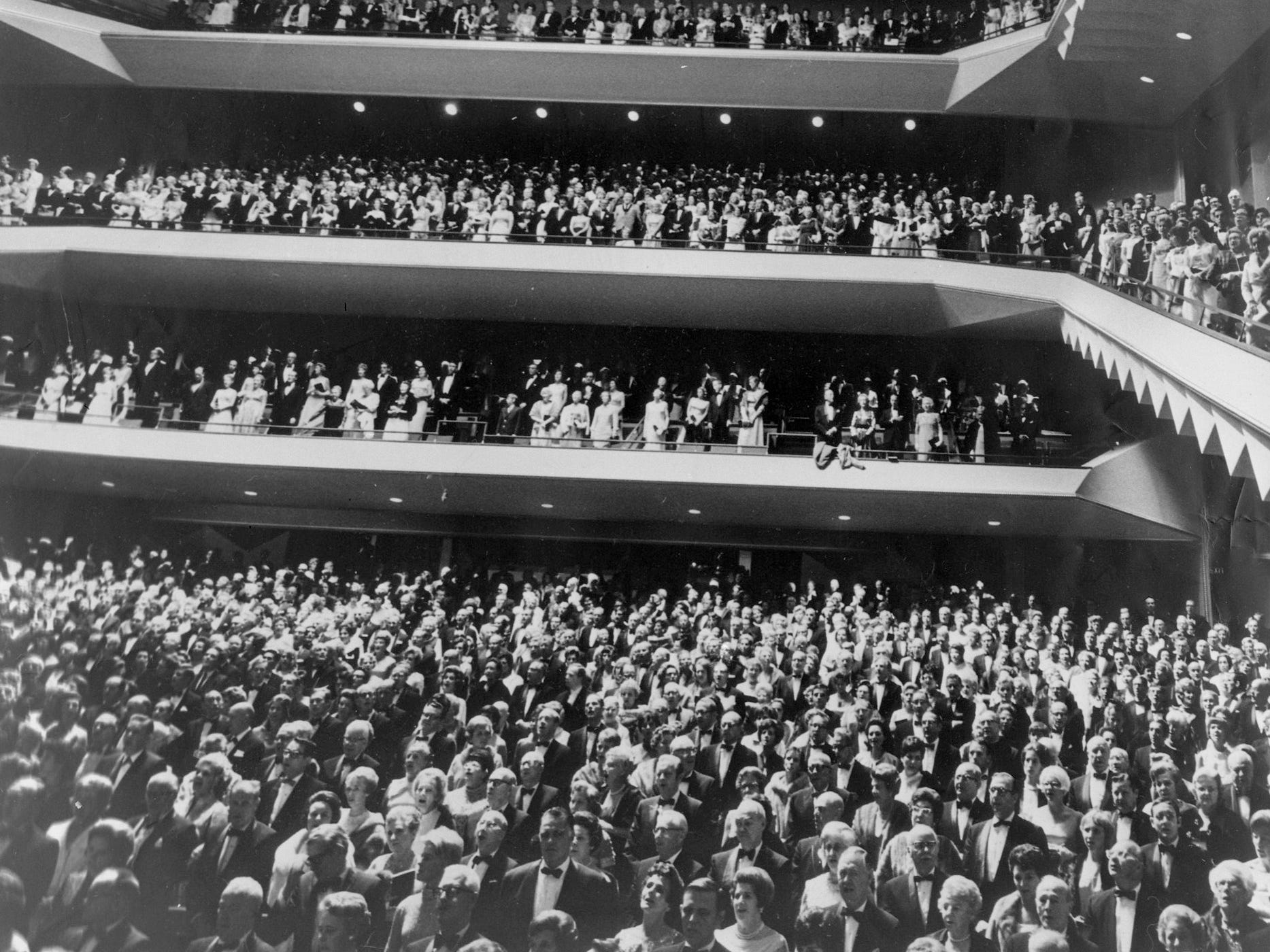 """Copy of a photo of a performance at the Performing Arts Center. This photo was in the Sept. 18 edition of the Sentinel with the caption """"Milwaukee's dignitaries stood as the Milwaukee symphony orchestra, led by Kenneth Schermerhorn, played """"The Star Spangled Banner"""" during the grand opening of the Performing Arts Center. The first night audience filled Uihlein hall to near capacity Wednesday night."""" Date is 9/18/1969. PAC transparency folder #690707"""