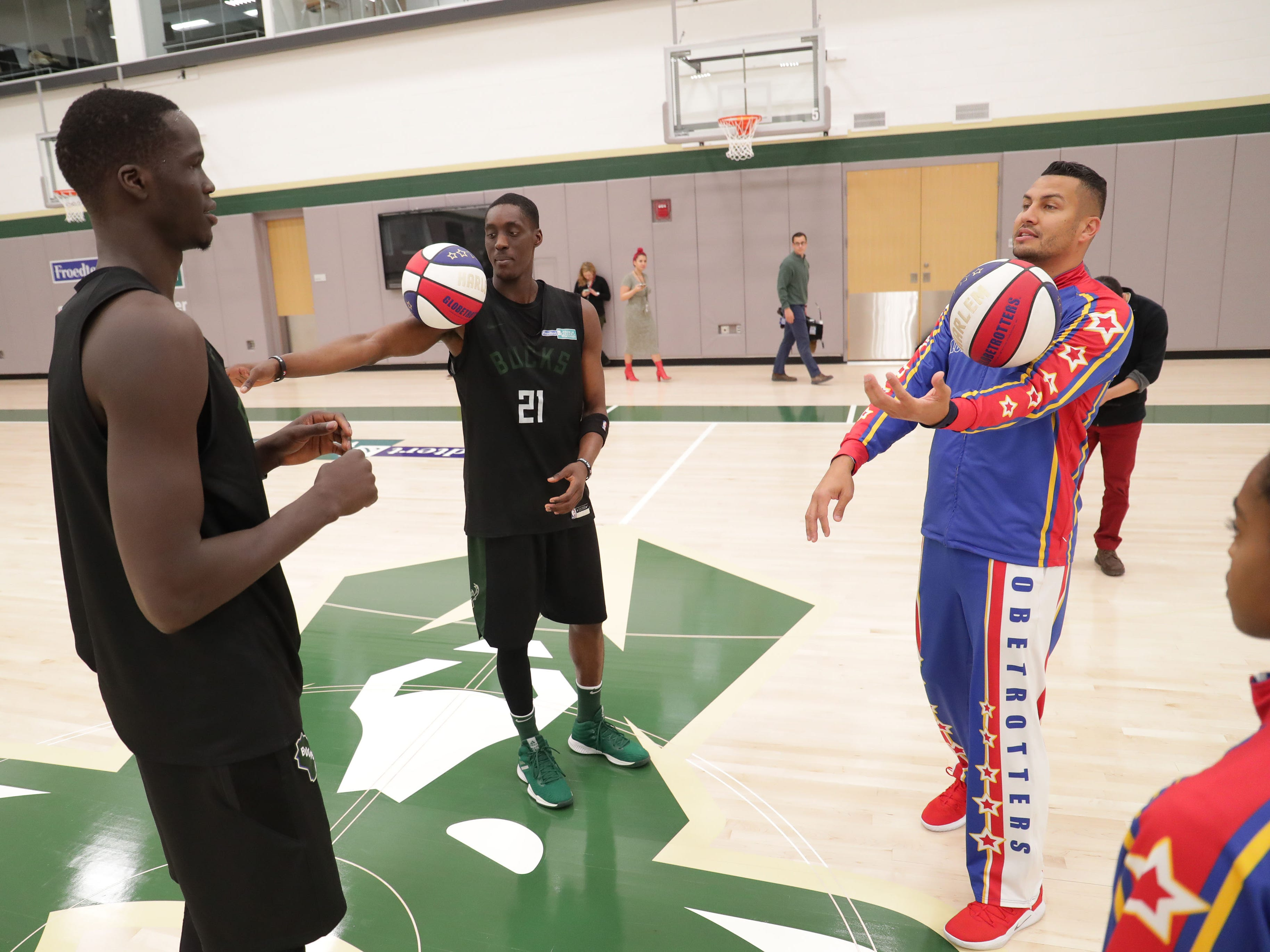 The Bucks' Thon Maker (left) and Tony Snell get a few pointers from the Harlem Globetrotters' Orlando El Gato Melendez.