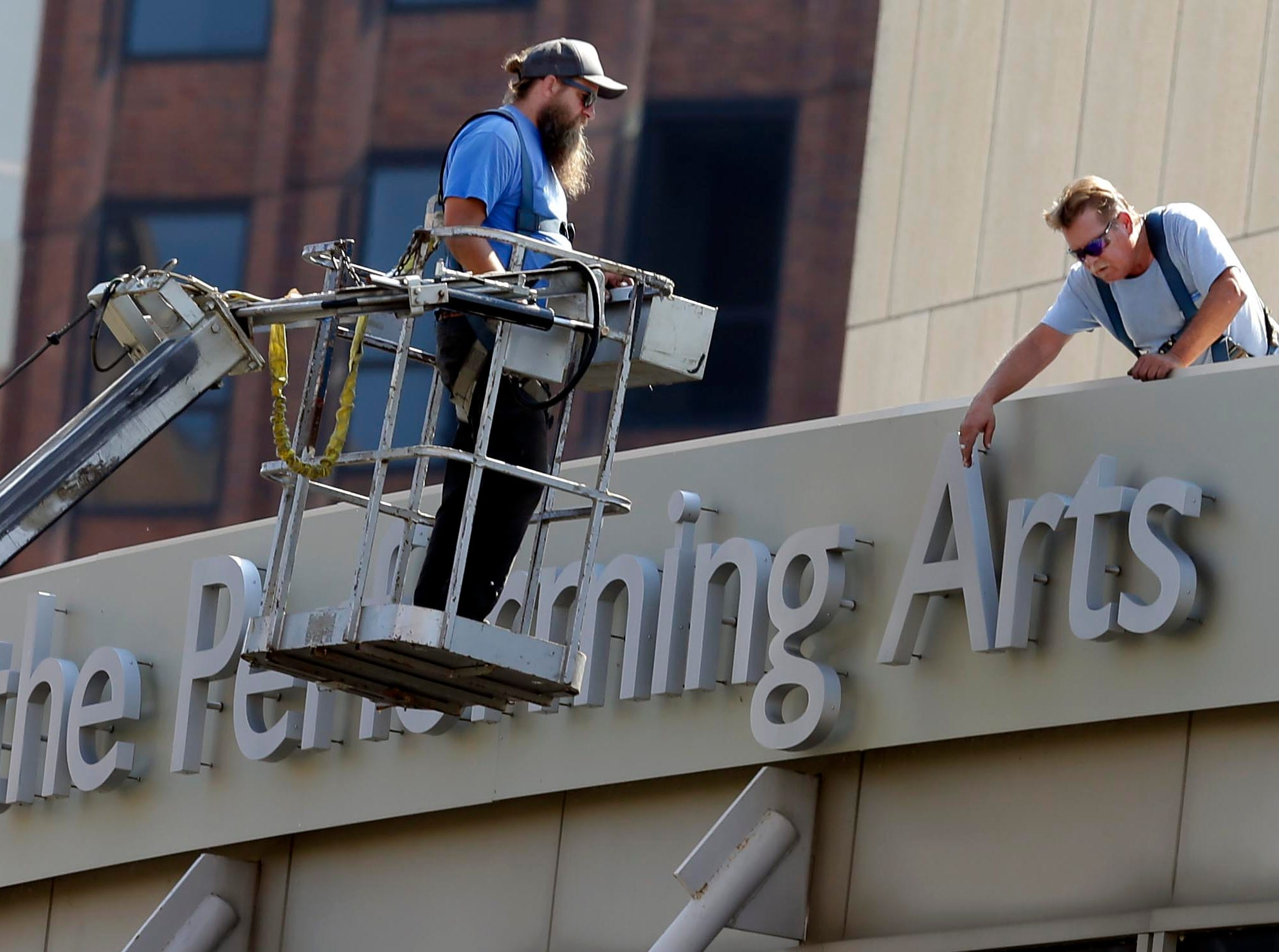 Two workers from Poblocki Sign Co. inspect the signage and lettering on the Marcus Center for the Performing Arts in Milwaukee, Wednesday, August 16, 2017.  Milwaukee Journal Sentinel photo by Rick Wood/RWOOD@JOURNALSENTINEL.COM