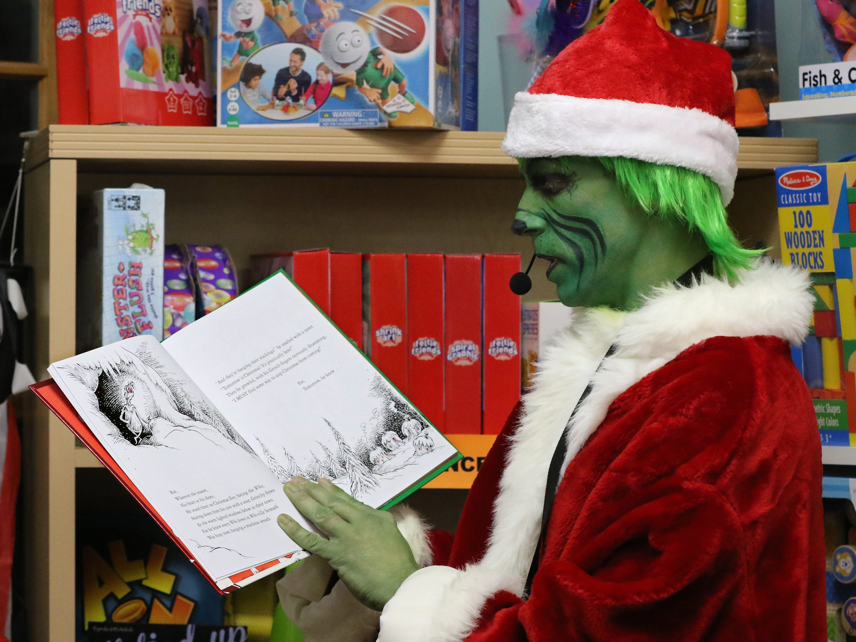 The Grinch, played by Rich Schoenholtz, reads from his favorite book to a packed store during Grinchmas in Pewaukee at Silly Willyz on Dec 6.