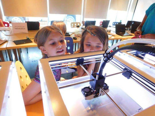 Two girls watch a 3-D printer during a MakerGirl session held at the University of Illinois.