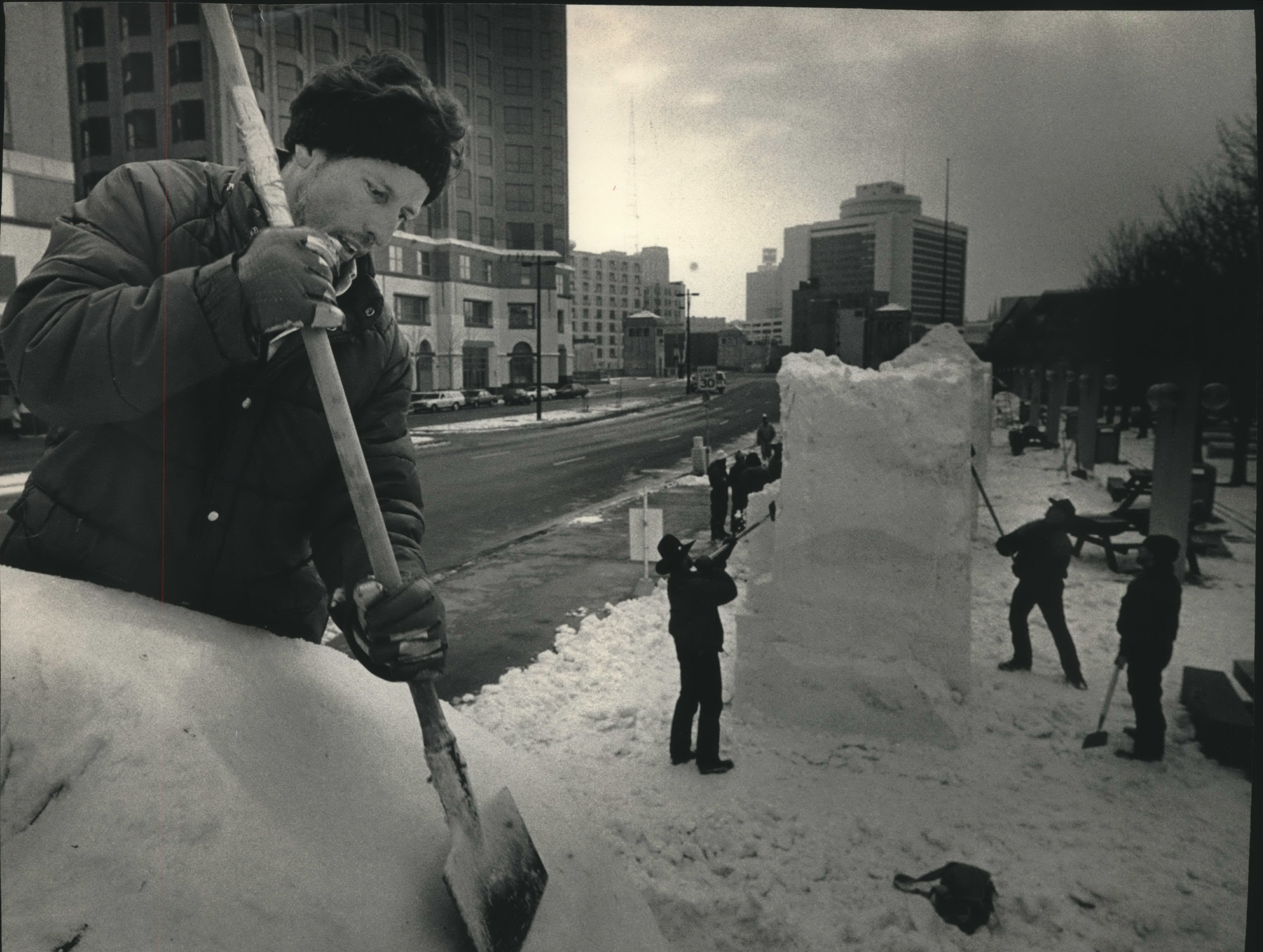 """Edger Suniga Jiminez, a member of the Costa Rica snow-sculpting team, works high atop the team's creation called """"Waiting,"""" which will depict humanity waiting for a better world. The sculpture is taking shape on East Kilbourn Avenue near North Water Street in front of the Performing Arts Center. Eighteen three-person teams from 14 nations are participating in the U.S. International Snow Sculpting Competition through Saturday on the PAC grounds and in Pere Marquette Park."""