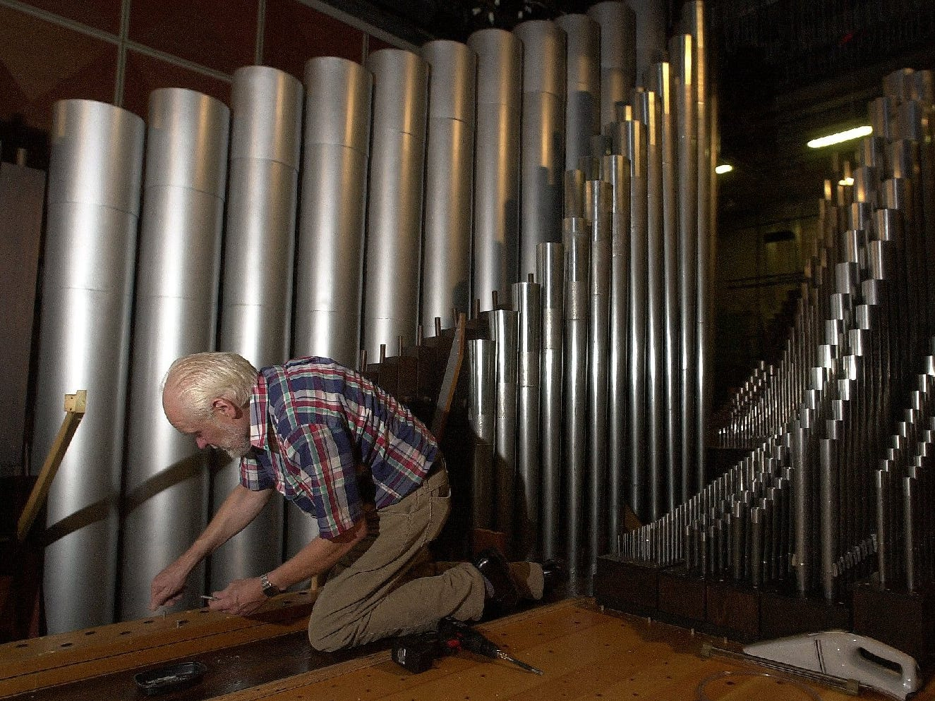 Organ technician Bill Hansen of Glendale, prepares to re-install one of roughly 3,000 pipes back into the pipe organ after cleaning it. The organ sits on a elevator floor under the Uihlein Hall floor and can lowered or raised for performances or cleaning.