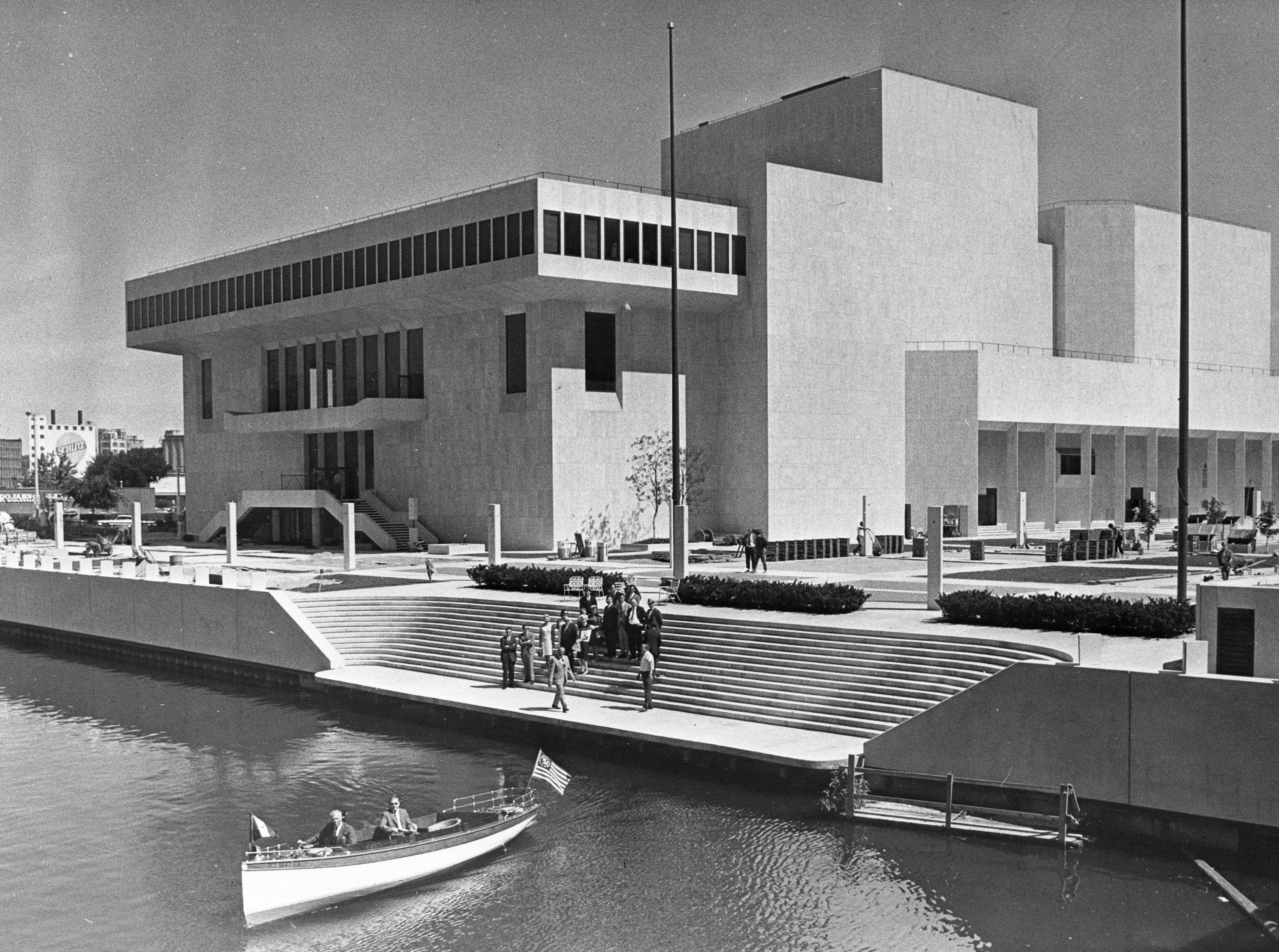 """Copy of a photo of the new Milwaukee Performing Arts Center (now known as the Marcus Center for the Performing Arts) or PAC at 929 N. Water St. Construction began on June 27, 1966. This photo was in the Aug. 19 edition of the Journal with the caption """"Landing Dedicated - Officials gathered Tuesday morning to watch as the first boat officially docked at Quarles landing at the Performing Arts Center. Riding in the boat were Atty. Louis Quarles (hidden) and Richard R. Teschner, president of the War Memorial Development Center. The landing, a gift from Quarles, and the Cudahy Memorial flag plaza which borders it, were dedicated at the ceremony. The plaza is the gift of the Patrick Cudahy Foundation. The boat was owned and piloted by C. R. Conlee.""""  Date is 8/19/1969. Neg. #69586  exterior, building, music, performance, stage, theater, Uihlein Hall, Todd Wehr hall, Peck Pavilion."""