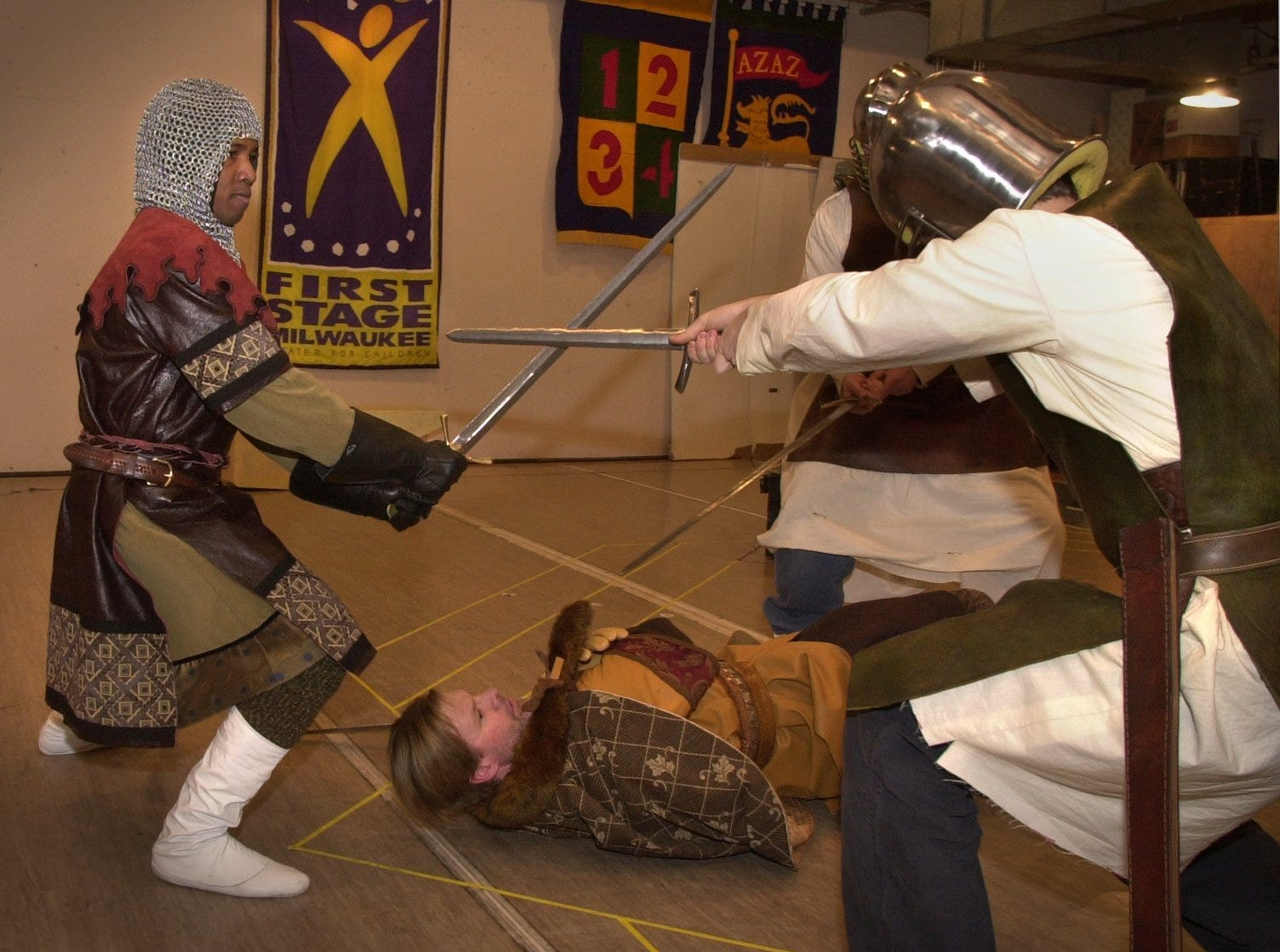 """Karim Ra, left as Lancelot, defends King Arthur, played by Peter Morse against Leodegrance, played by D. Lance Marsh and Kay as Michaelangello Matarrese (right) during a rehearsal of First Stage's """"Arthur-The Boy Who Would Be King,"""" at the Marcus Center for the Performing Arts, Wednesday, February 27, 2001."""