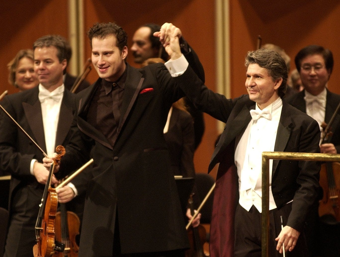 Andreas Delfs, Milwaukee Symphony Orchestra conductor, right, and guest soloist violinist Nikolaj Znaider take a curtain call after performing Friday, Feb. 6, 2004, at the Marcus Performing Arts Center. Znaider, 28, lived in Denmark before moving to New York.