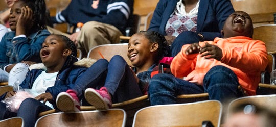 Twins Mahlori and Meghon Bradshaw and Amari Brooks  laugh while watching the Harlem Globetrotters game as part of a field trip for the twins at Peter Crump Elementary School in Montgomery, Ala., on Thursday evening December 6, 2018.
