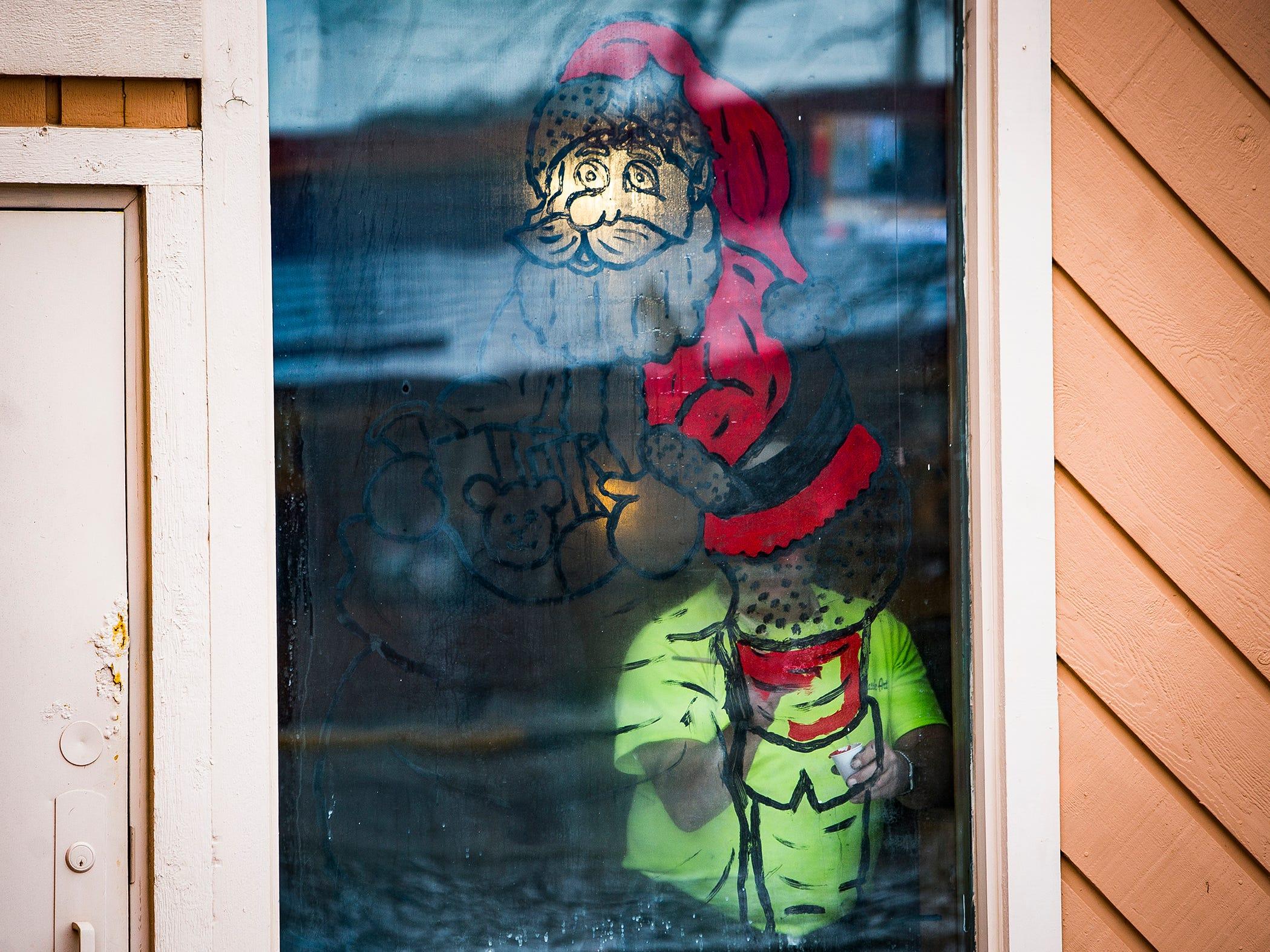 Ron Davis of Classic Art Co. paints the windows of Peurto Vallarta on Tillotson Avenue. Davis has been a window painter for nearly thirty years.