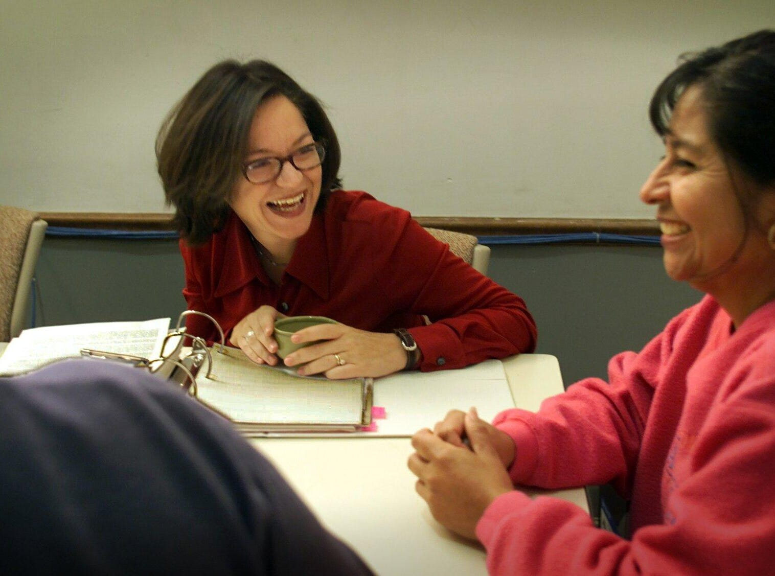 Renata Soto laughs with Herlinda Diaz during a meeting of the Woodbine Community Organization, where she serves on the Hispanic advisory committee, on Nov. 22, 2000.
