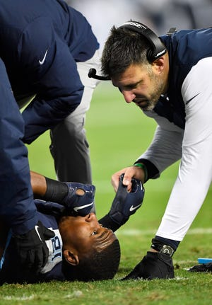Titans coach Mike Vrabel tends to injured tight end Jonnu Smith (81) in the second quarter of Thursday's game.
