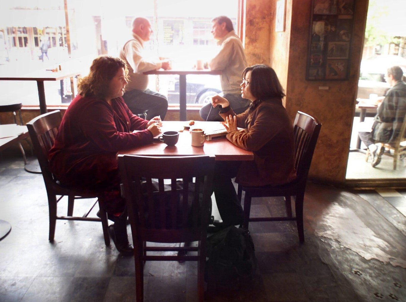 Mary Griffin, left, and Renata Soto combine coffee and work at Fido's in Hillsboro Village as they plan their Spanish language radio program Nov. 24, 2000.