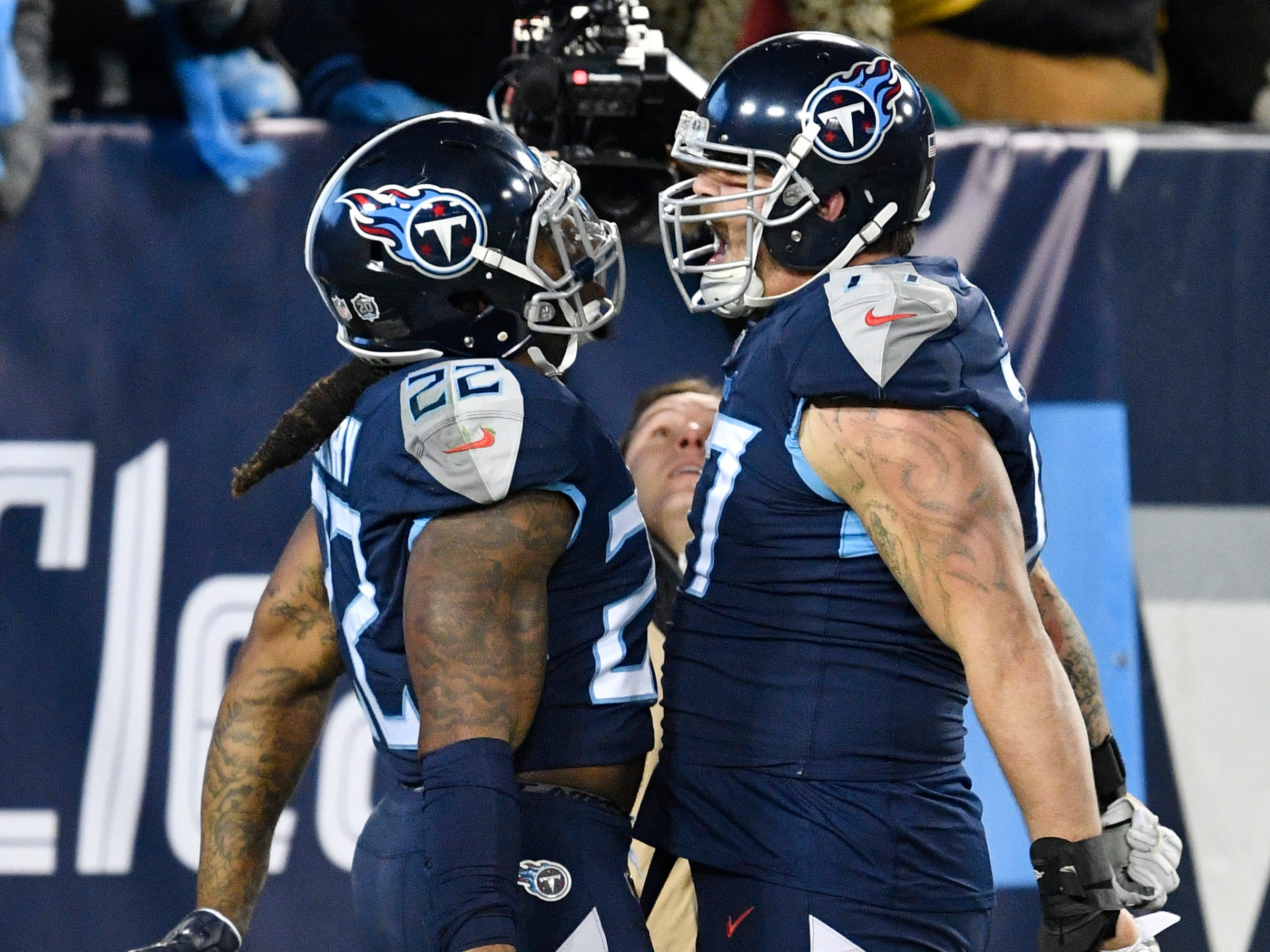 Titans running back Derrick Henry (22) celebrates his 99-yard touchdown with offensive tackle Taylor Lewan (77) in the second quarter at Nissan Stadium Thursday, Dec. 6, 2018, in Nashville, Tenn.