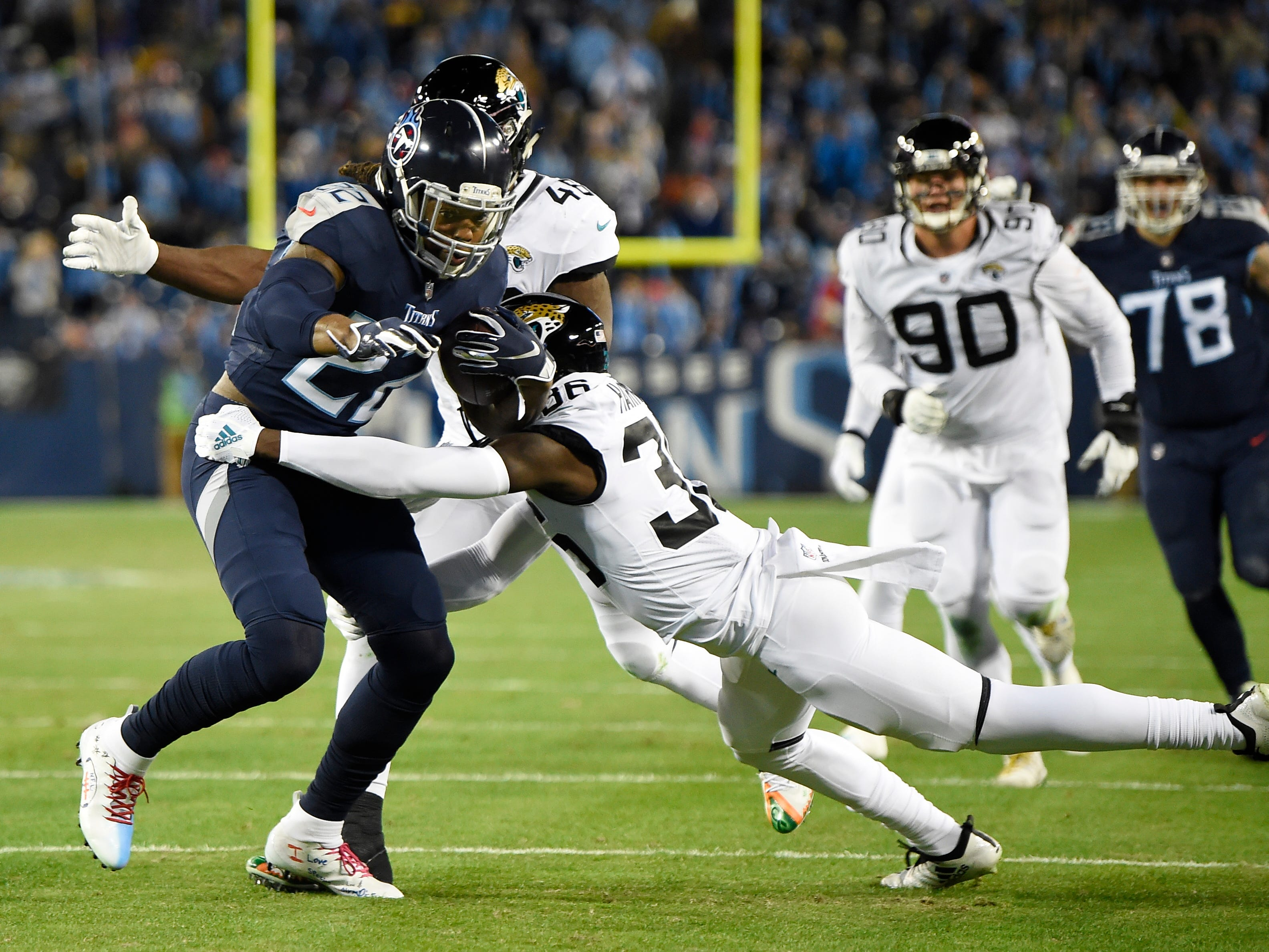 Titans running back Derrick Henry (22) rushes for a first down defended by Jaguars safety Ronnie Harrison (36) in the first quarter at Nissan Stadium Thursday, Dec. 6, 2018, in Nashville, Tenn.