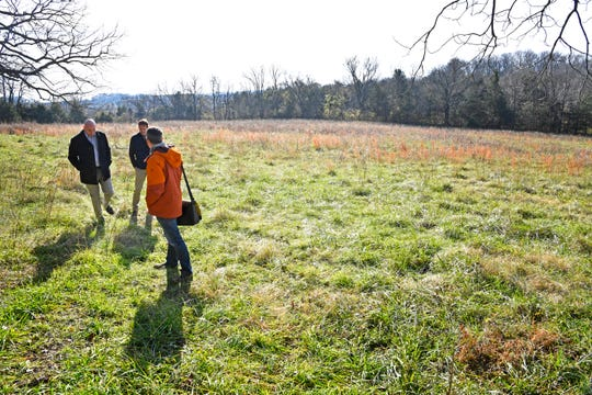Architects Paul Bass, Greg Gamble and Kyle Kramer wander around an open field where a mixed-use development will soon be built near the John Carothers home in Franklin.