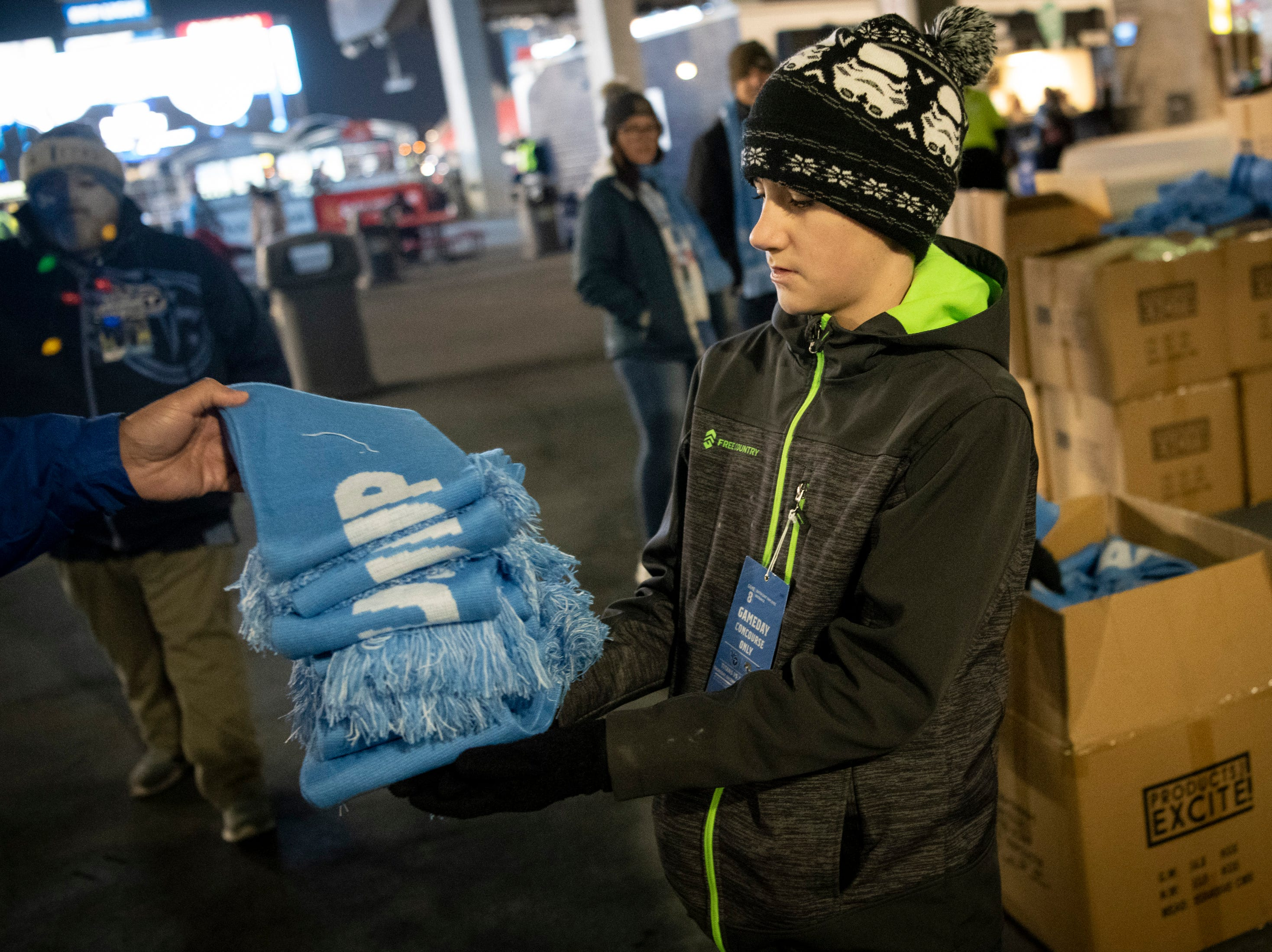 Wesley Gransmaison, 11, hands out scarfs to fans before the game between the Tennessee Titans and the Jacksonville Jaguars at Nissan Stadium in Nashville, Tenn., Thursday, Dec. 6, 2018.