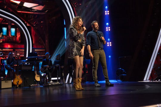 "Jamie Floyd and host Graham Bunn talk on stage during a taping of an episode of USA Network show ""Real Country."""