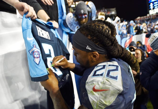 Titans running back Derrick Henry (22) signs a jersey after his team's 30-9 win Thursday.