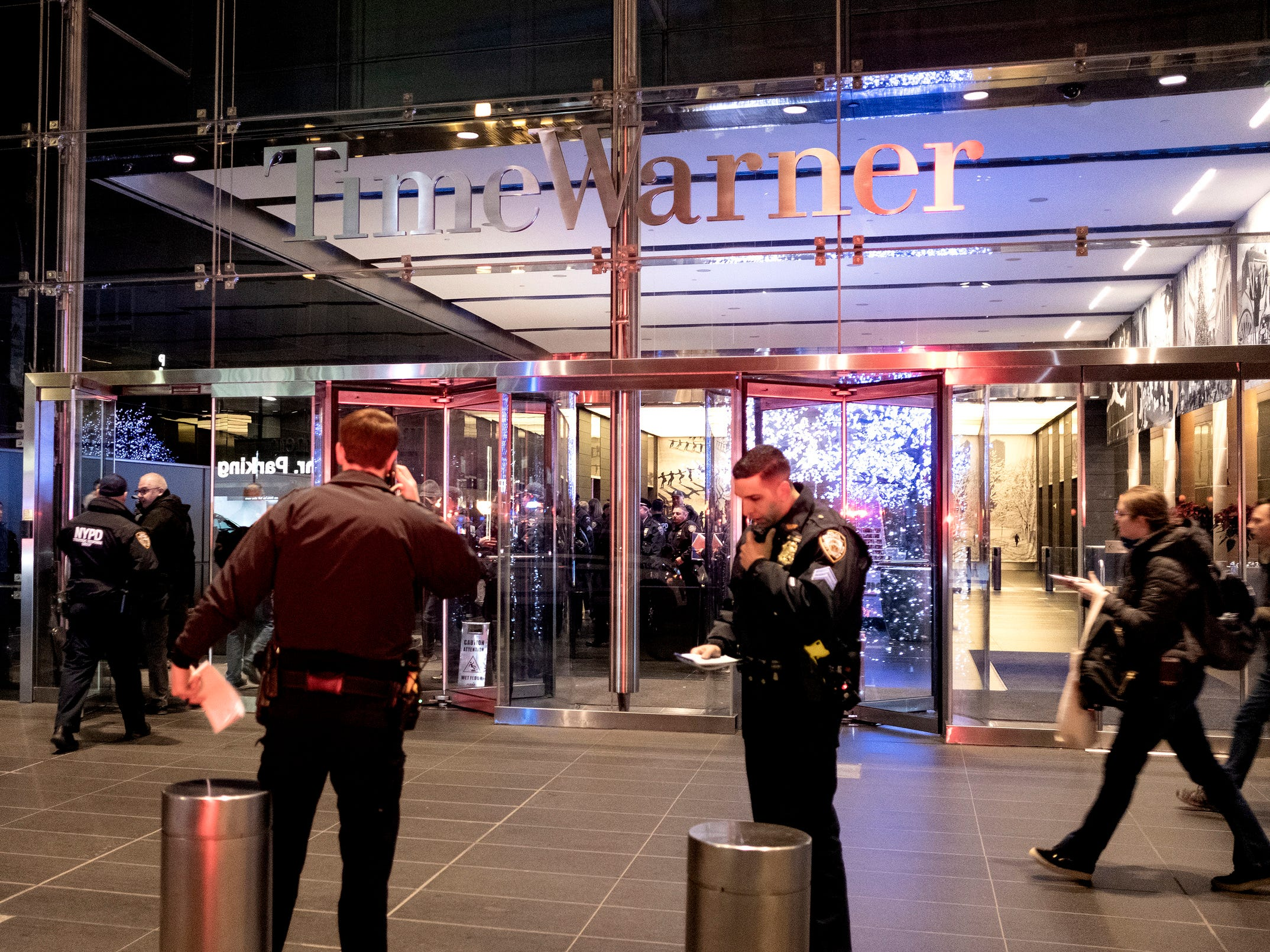 After it was determined the building was safe, New York City police officers stand by at the Time Warner Center as people reenter the lobby in New York Thursday, Dec. 6, 2018, after a bomb threat was called into the building and occupants were evacuated, including CNN employees. Police units swept the building with the NYPD bomb squad on standby.