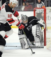 New Jersey Devils center Travis Zajac, left, tries to get a shot past Los Angeles Kings goaltender Jonathan Quick during the first period of an NHL hockey game Thursday, Dec. 6, 2018, in Los Angeles.