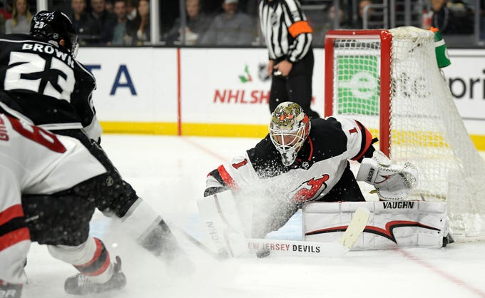 Los Angeles Kings right wing Dustin Brown, left, tries to get a shot past New Jersey Devils goaltender Keith Kinkaid during the second period of an NHL hockey game Thursday, Dec. 6, 2018, in Los Angeles.
