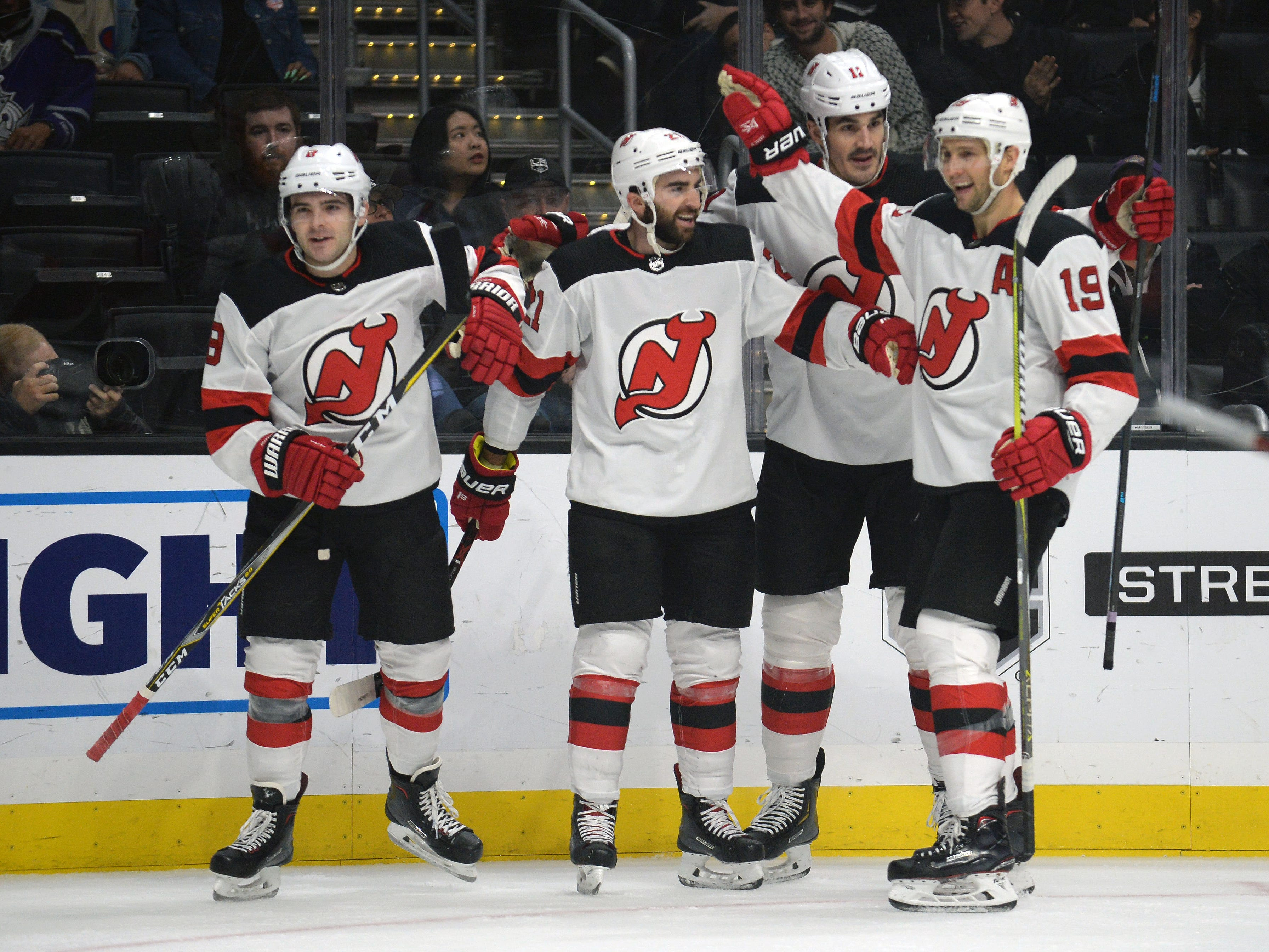 December 6, 2018; Los Angeles, CA, USA; New Jersey Devils right wing Kyle Palmieri (21) celebrates with defenseman Will Butcher (8) center Travis Zajac (19) and defenseman Ben Lovejoy (12) his goal scored against the Los Angeles Kings during the first period at Staples Center.