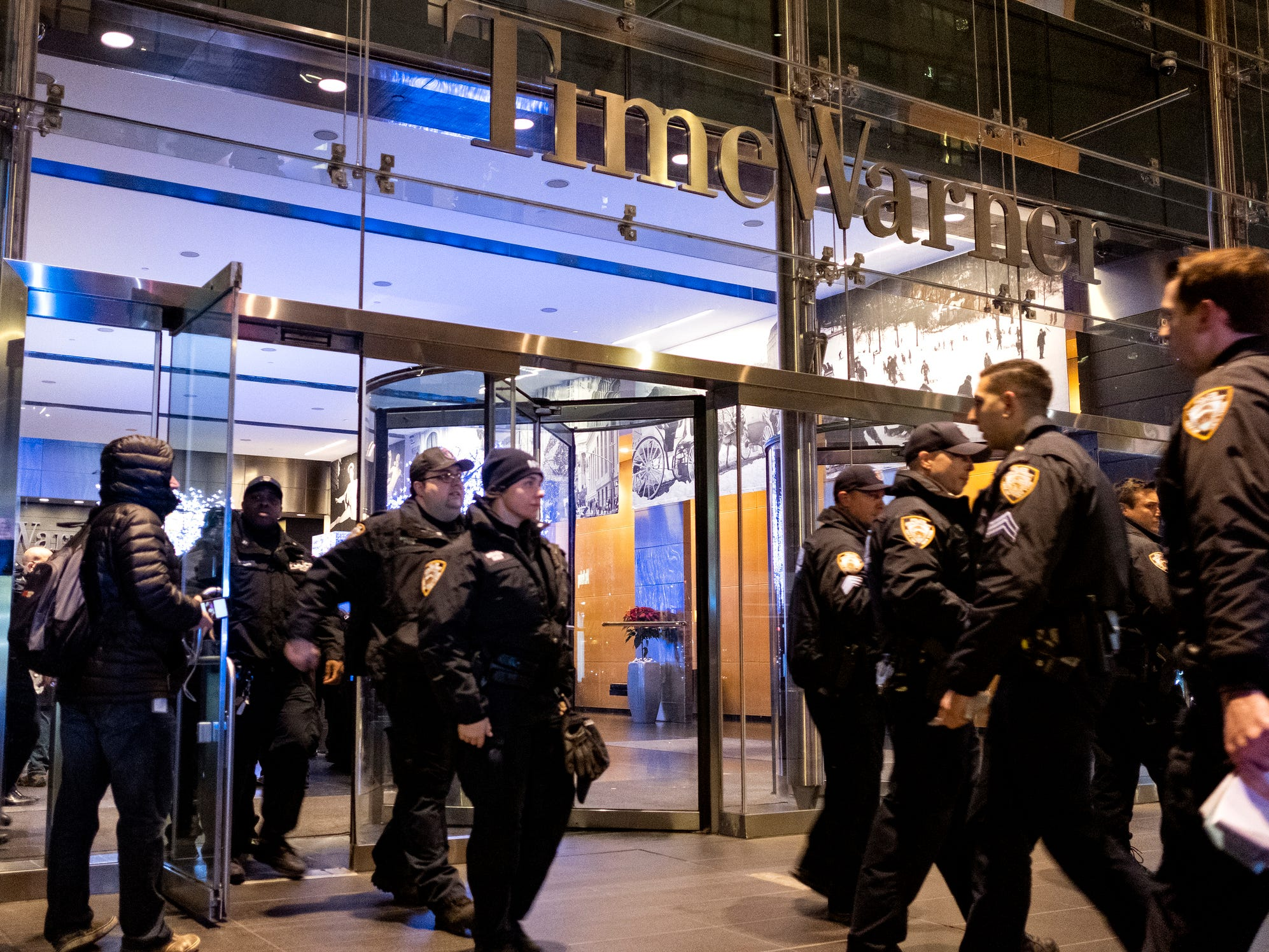 After the building was determined safe, New York City police officers walk from the Time Warner Center in New York Thursday, Dec. 6, 2018, after a bomb threat was called into the building and occupants were evacuated, including CNN employees.