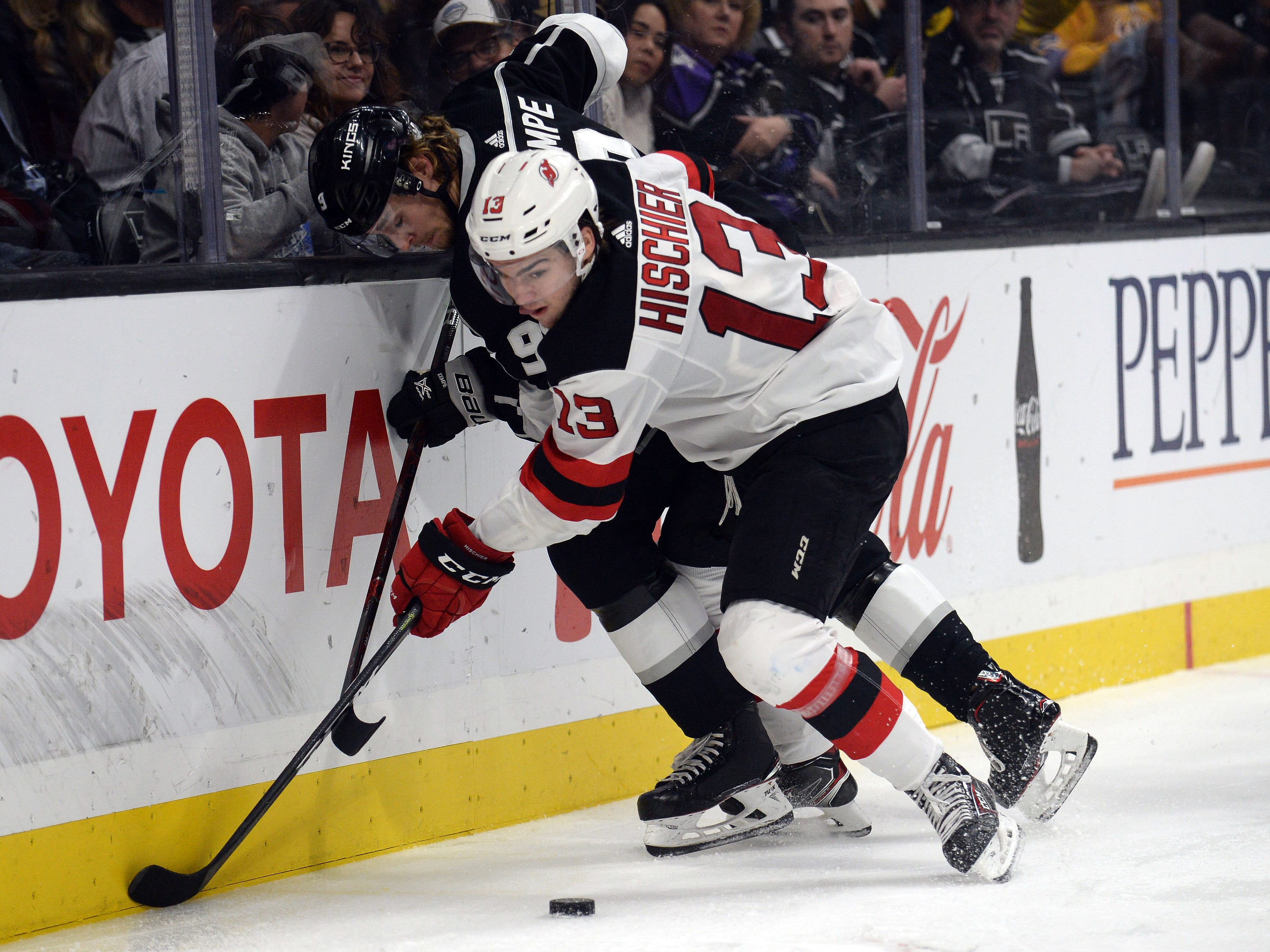 December 6, 2018; Los Angeles, CA, USA; New Jersey Devils center Nico Hischier (13) plays for the puck against Los Angeles Kings center Adrian Kempe (9) during the second period at Staples Center.