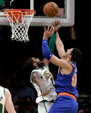 New York Knicks center Enes Kanter (00) goes to the basket against Boston Celtics guard Kyrie Irving (11) during the second quarter of an NBA basketball game, Thursday, Dec. 6, 2018, in Boston.