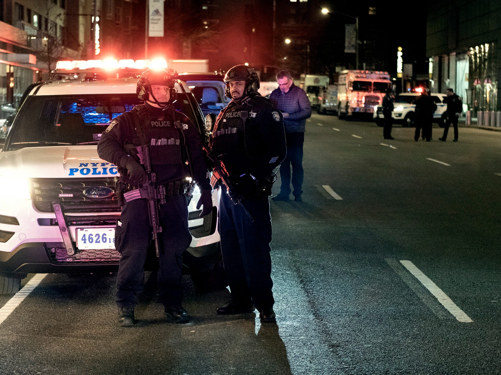 New York City police officers stand by near the Time Warner Center in New York Thursday, Dec. 6, 2018, after a bomb threat was called into the building and occupants were evacuated, including CNN employees. Police units swept the building with the NYPD bomb squad on standby.
