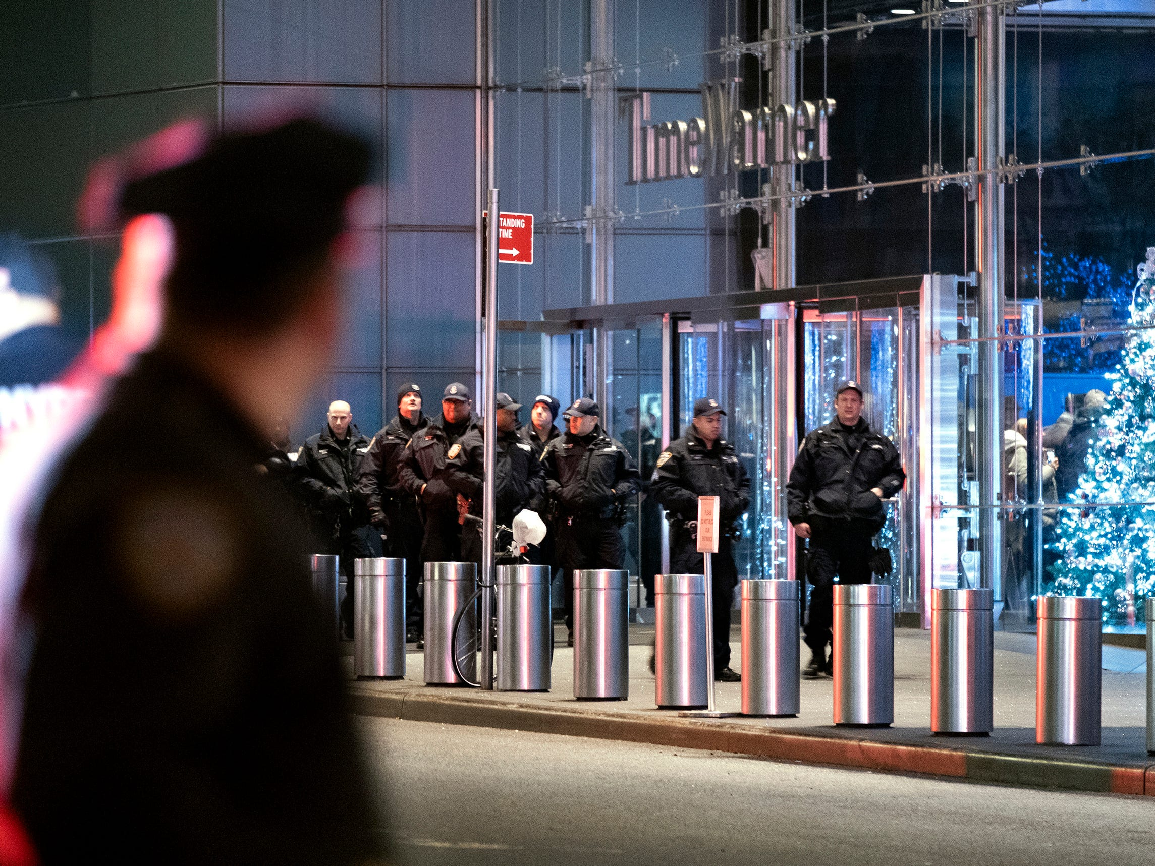 New York City police officers walk near the Time Warner Center Thursday, Dec. 6, 2018, after a bomb threat was called into the building and occupants were evacuated, including CNN employees. Police have given the all-clear after a phoned in bomb threat forced the evacuation of CNN's offices in New York.