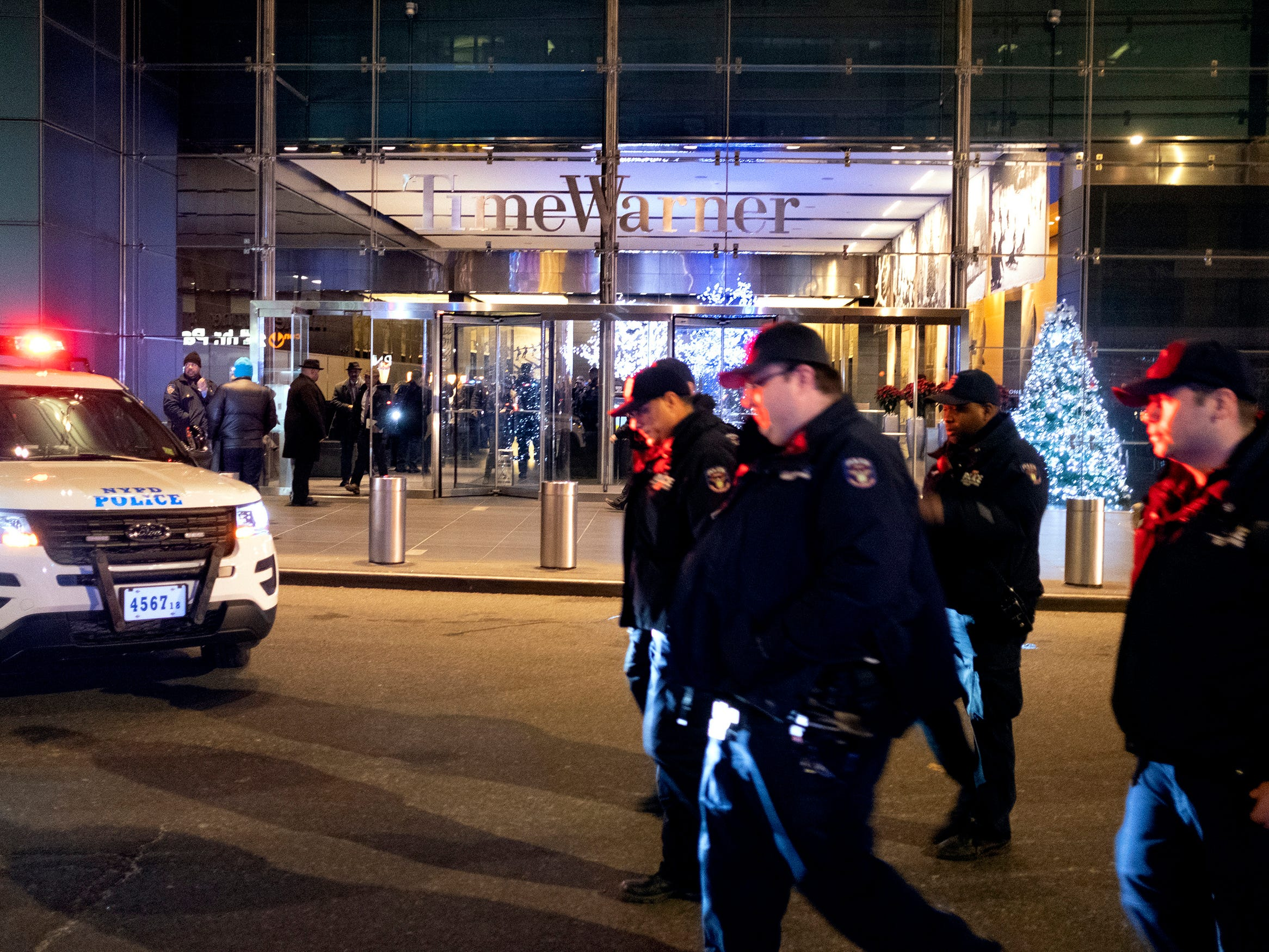 After the building was determined safe, New York City police officers walk from the area of Time Warner Center in New York Thursday, Dec. 6, 2018, after a bomb threat was called into the building and occupants were evacuated, including CNN employees.