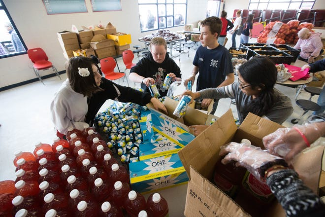 Students at Lynn Middle School organize drinks for a mobile food bank at Lynn Middle School on Wednesday, December 5, 2018.