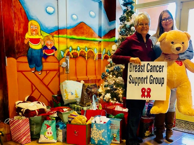 Josephine Wiskowski, left, Breast Cancer Support Group co- chair, provides children's gifts to Gisela Dominquez, right, of Jardín de los Niños.
