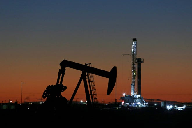 In this Oct. 9, 2018, file photo, an oil rig and pump jack work along the roadside of FM 1788 in Midland, Texas.  With more barrels of oil being pumped monthly from the Permian Basin, New Mexico is among the nation's top producing states.