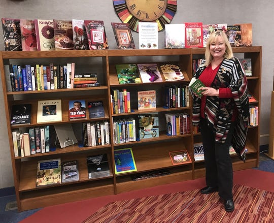Library Director Cassandra Arnold with the new book sale shelves at Carlsbad Public Library.