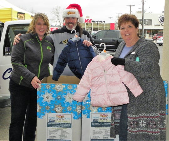 From left Stephanie Hale of Thrive in Southern New Mexico, Mike Mason of Burt Broadcasting and Tammie Reynolds of Burt Broadcasting hold up donated coats at Thrive's Koats for Kids coat donation drive at First National Bank Friday. The coat drive is ongoing.