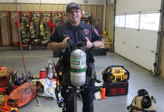 AFD Lieutenant John Stroope holds aloft one of the department's current SCBAs, which weigh about 35 pounds.