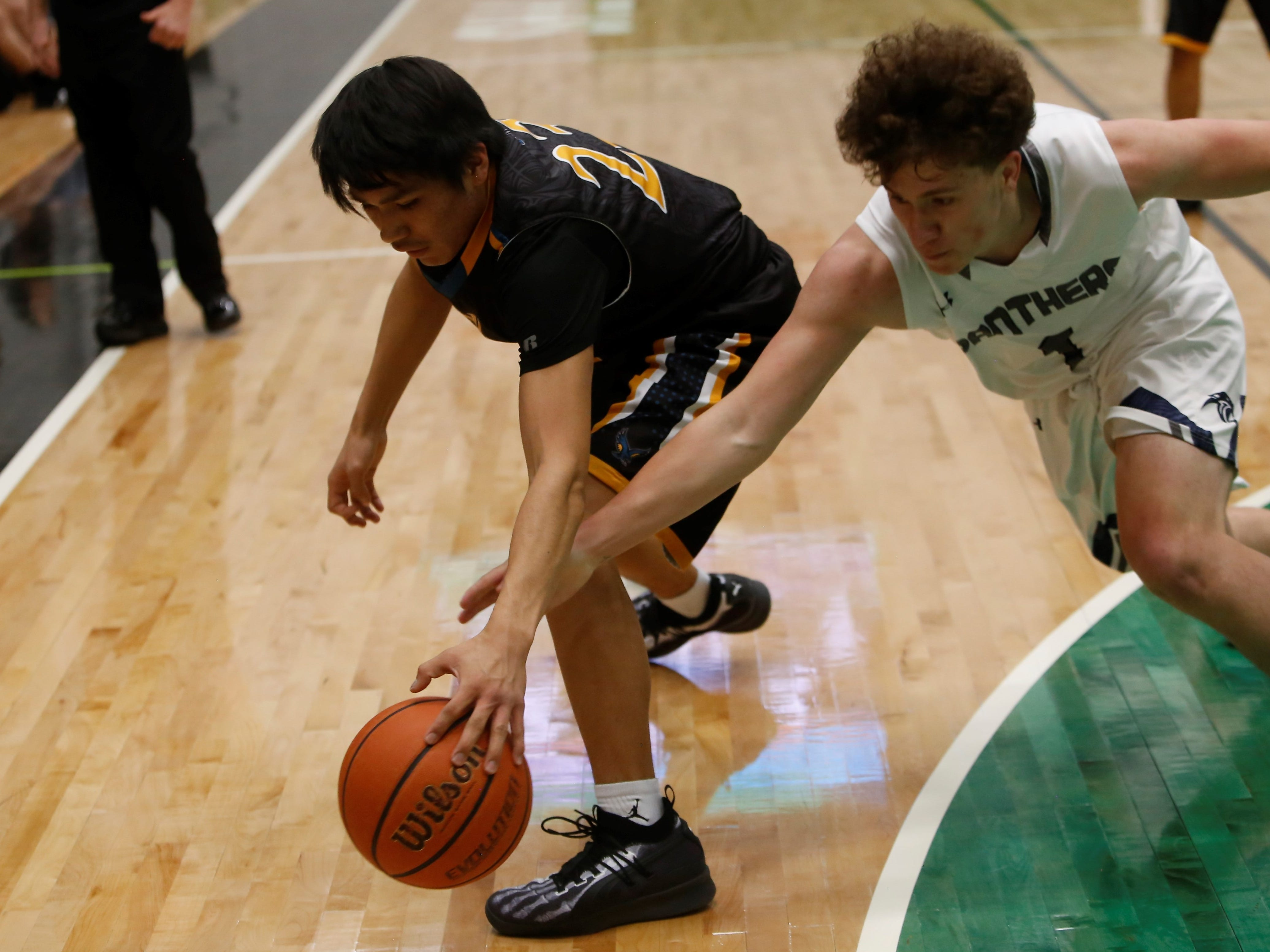 Navajo Prep's Trejan Clichee tries to keep control of the ball near the baseline against Piedra Vista's Jalen Woods during the Marv Sanders Invitational quarterfinals Thursday at Scorpion Arena in Farmington.