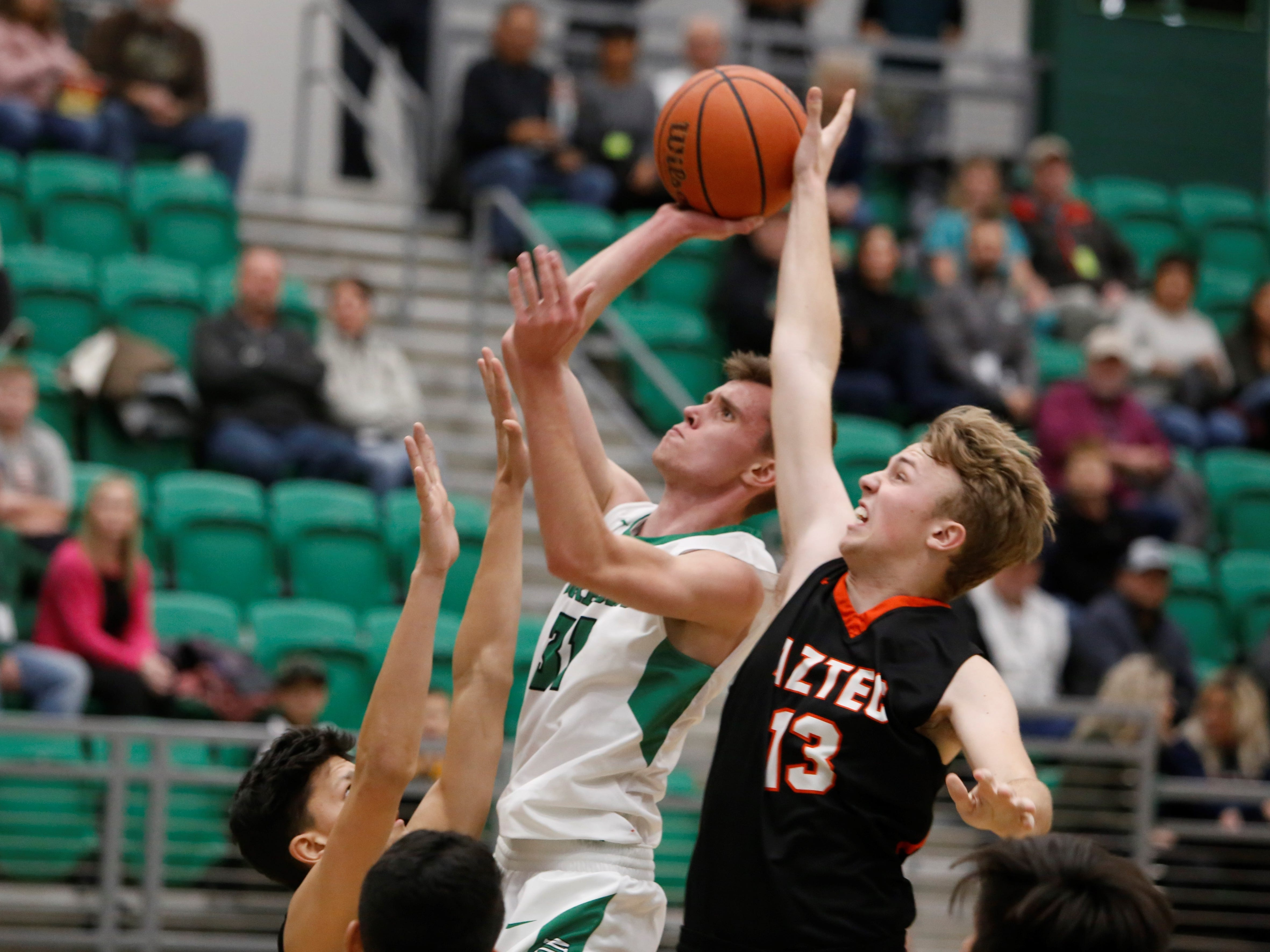 Aztec's Dom Faverino blocks a shot attempt by Farmington's Jacob Gillen during Thursday's Marv Sanders Invitational quarterfinals at Scorpion Arena in Farmington.