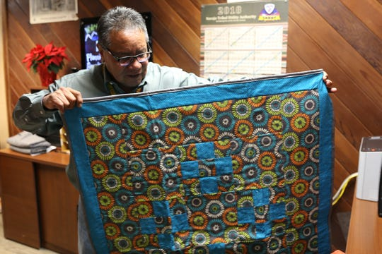 Nenahnezad Chapter community services coordinator Arthur Bavaro shows a quilt that was made during last year's quilting program.