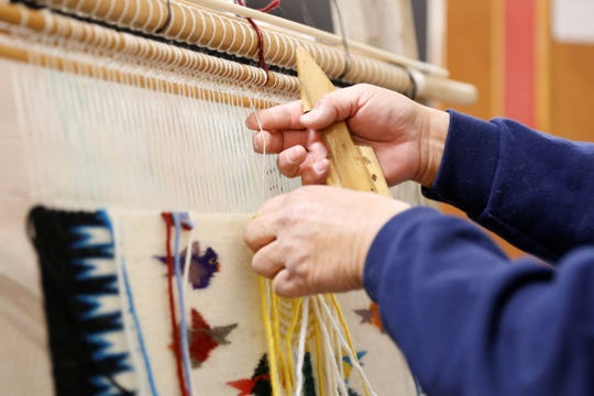 Pauline Mescal arranges the yarn for her Tree of Life rug on Wednesday at the Nenahnezad Chapter house.