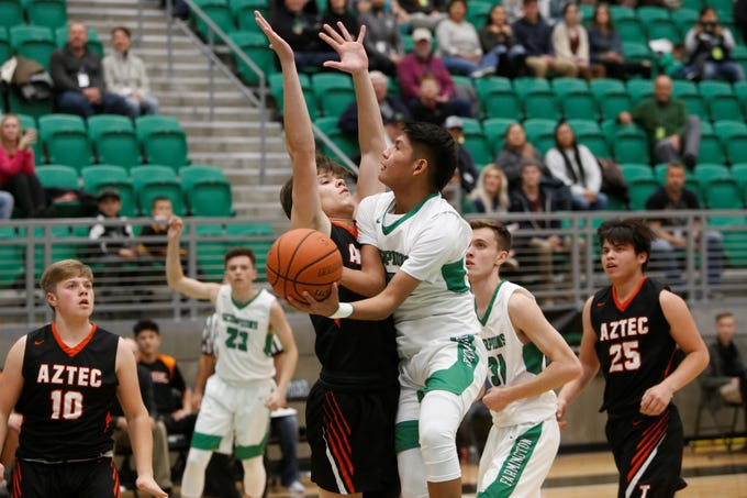 Farmington's Jordan Beyale drives to the paint and makes contact with Aztec's Gabe Wood during Thursday's Marv Sanders Invitational quarterfinals at Scorpion Arena in Farmington.